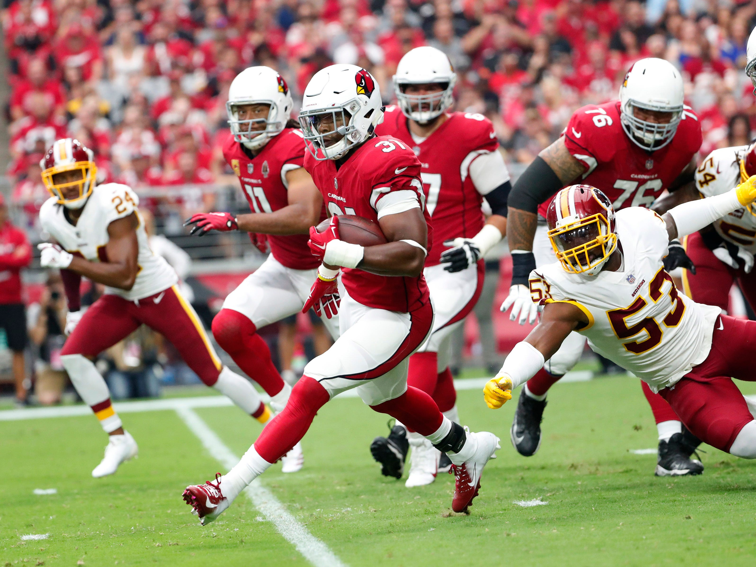 Arizona Cardinals running back David Johnson (31) runs through a hole against the Washington Redskins during the first quarter at State Farm Stadium in Glendale, Ariz. September 9. 2018.