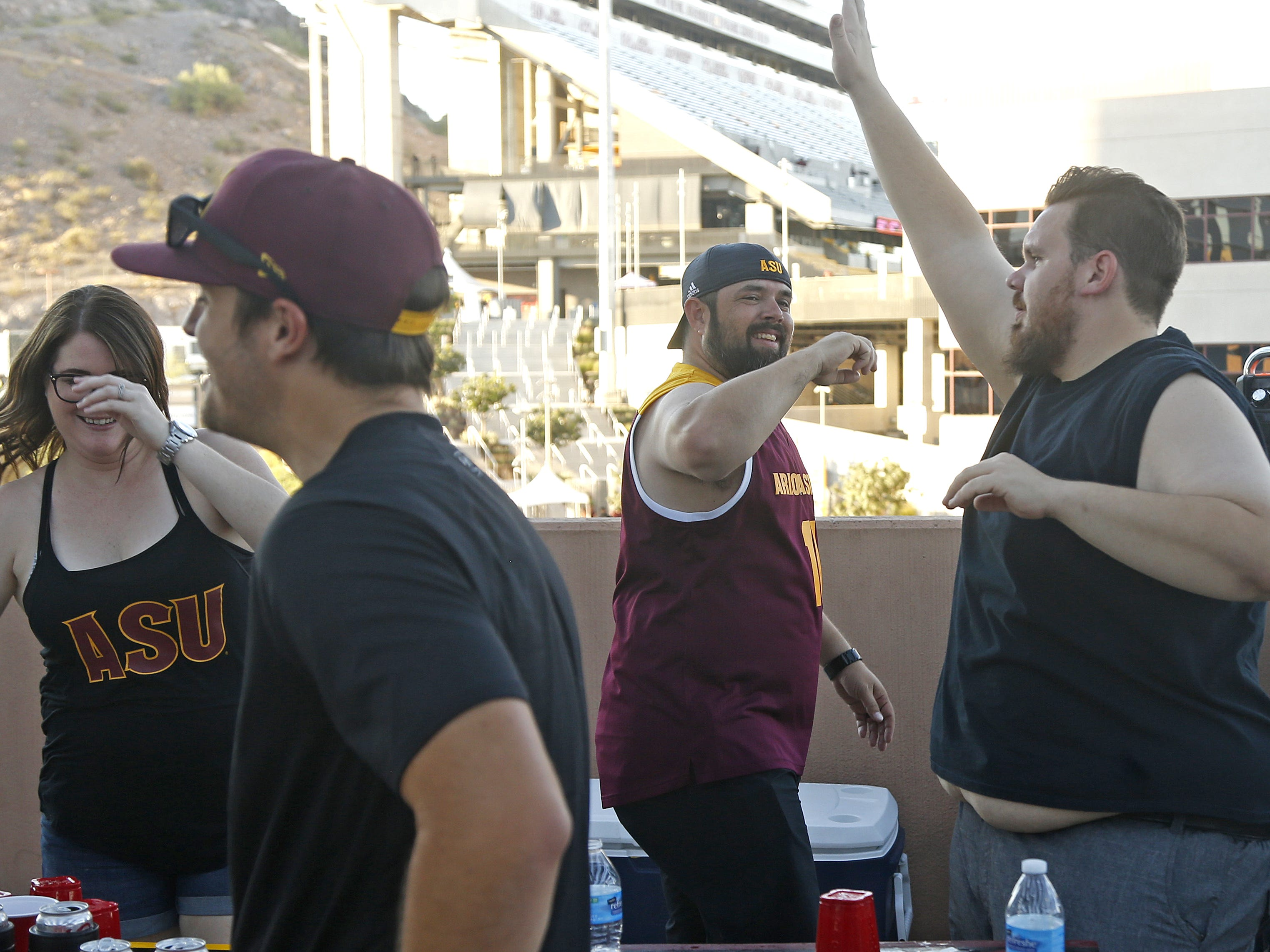 Adam Ali (center) celebrates winning a game of what they call flip pong before an ASU game against Michigan State at Sun Devil Stadium in Tempe, Ariz. on Sept. 8, 2018.