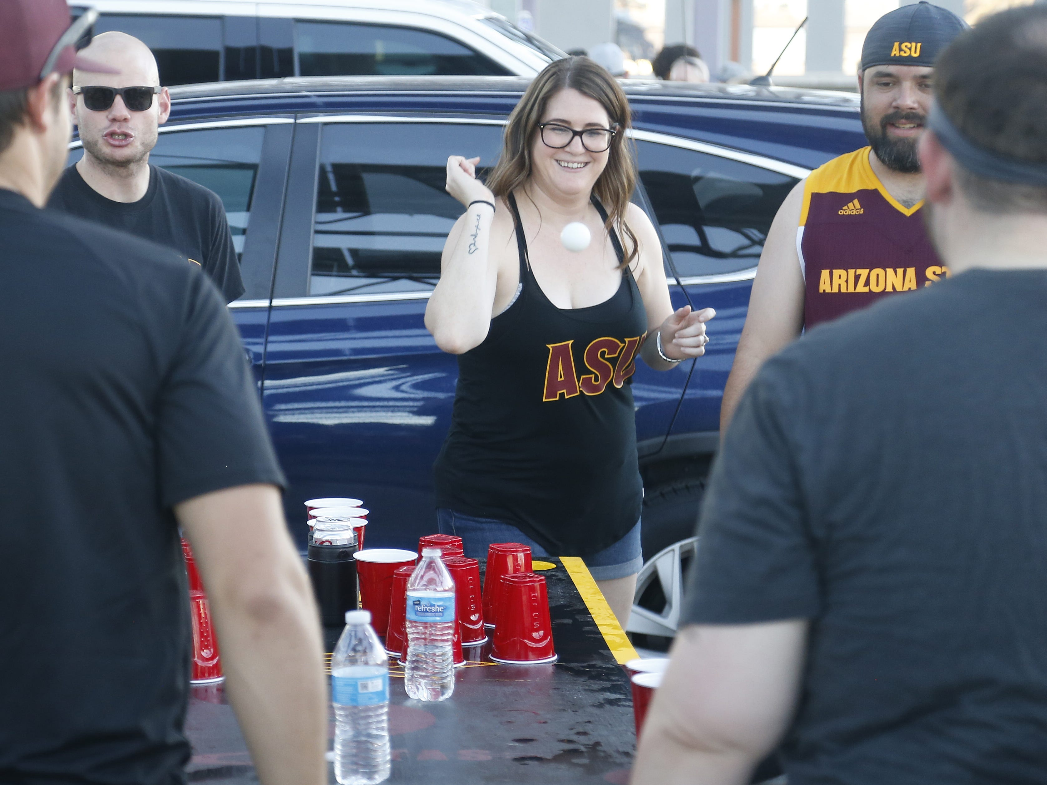 Jen Selleck (R) throws a ping pong ball for their game of flip pong with her friends before an ASU game against Michigan State at Sun Devil Stadium in Tempe, Ariz. on Sept. 8, 2018.
