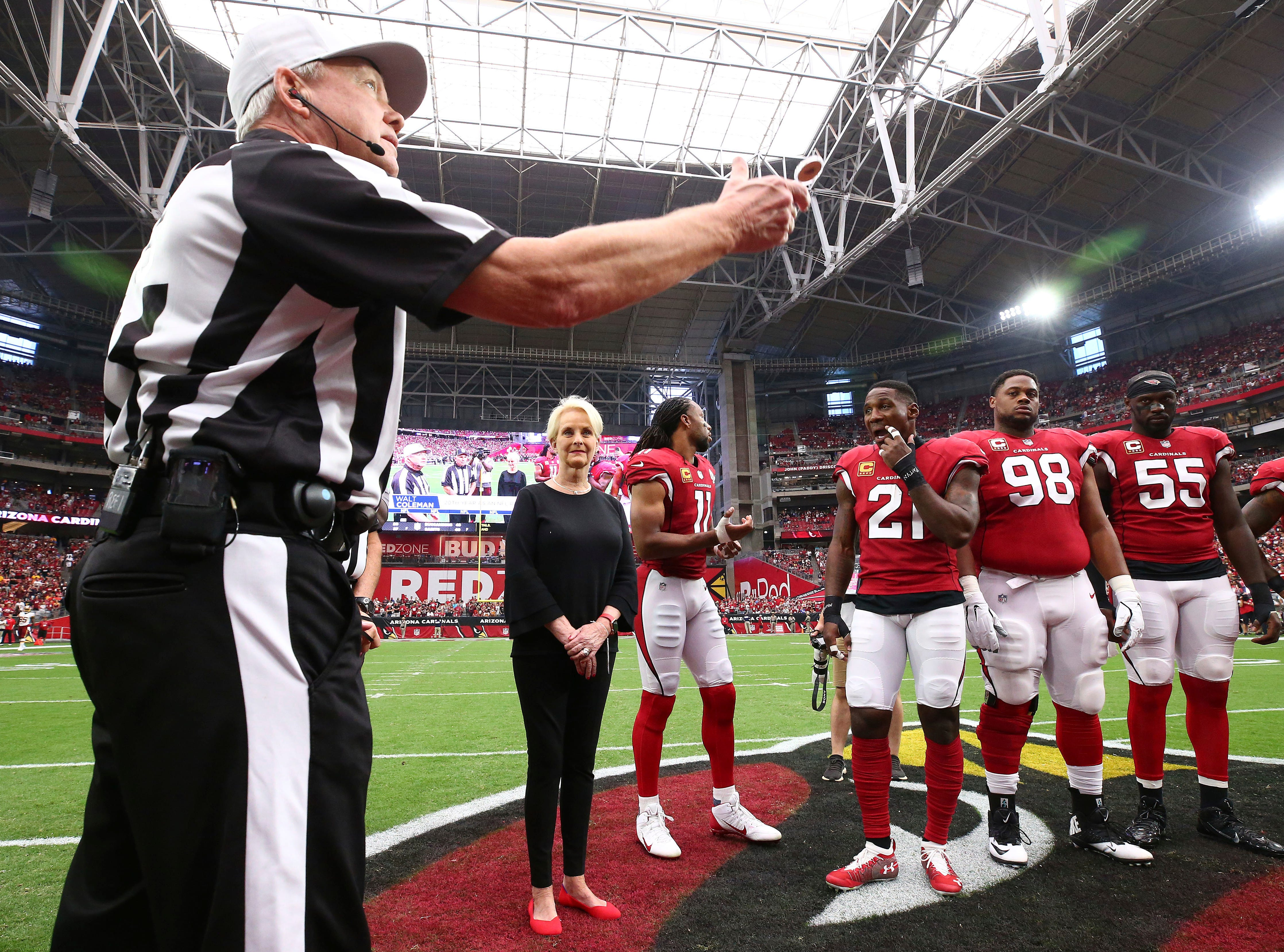 Cindy McCain, wife of the late U.S. Sen. John McCain, R-Ariz., stands with Arizona Cardinals' Larry Fitzgerald (11), Patrick Peterson (21), Corey Peters (98) and Chandler Jones (55) as an honorary team captain as referee Walt Coleman tosses the coin prior to an NFL football game against the Washington Redskins,  Sept. 9, 2018, in Glendale, Ariz.