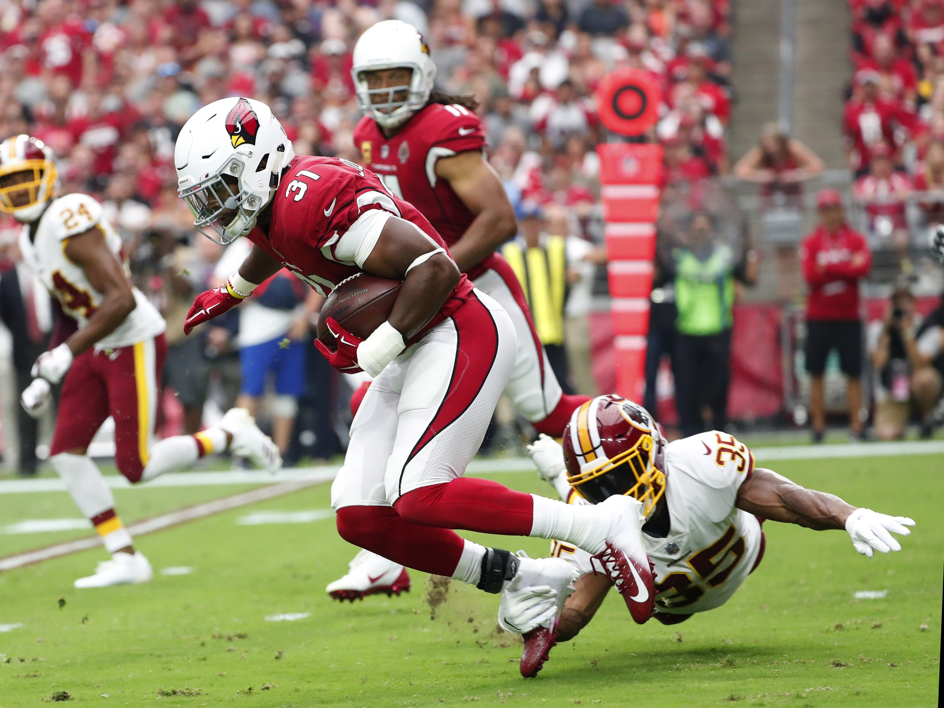 Arizona Cardinals running back David Johnson (31) is tackled by Washington Redskins defensive back Montae Nicholson (35) during the first quarter at State Farm Stadium in Glendale, Ariz. September 9. 2018.