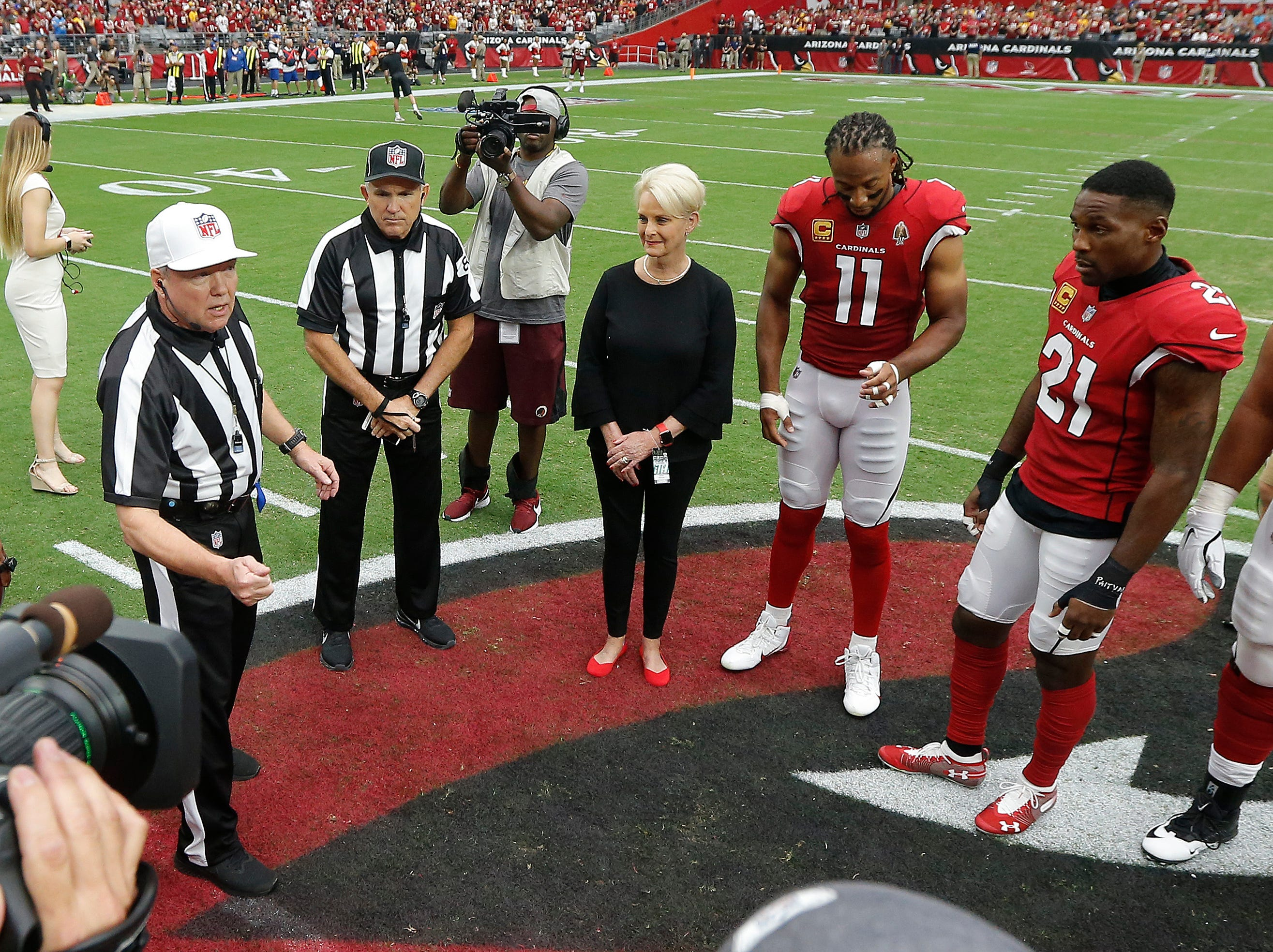 Cindy McCain, wife of the late U.S. Sen. John McCain, R-Ariz., stands with Arizona Cardinals players' Larry Fitzgerald (11) and Patrick Peterson (21) as an honorary team captain during the coin toss prior to an NFL football game against the Washington Redskins, Sept. 9, 2018, in Glendale, Ariz.