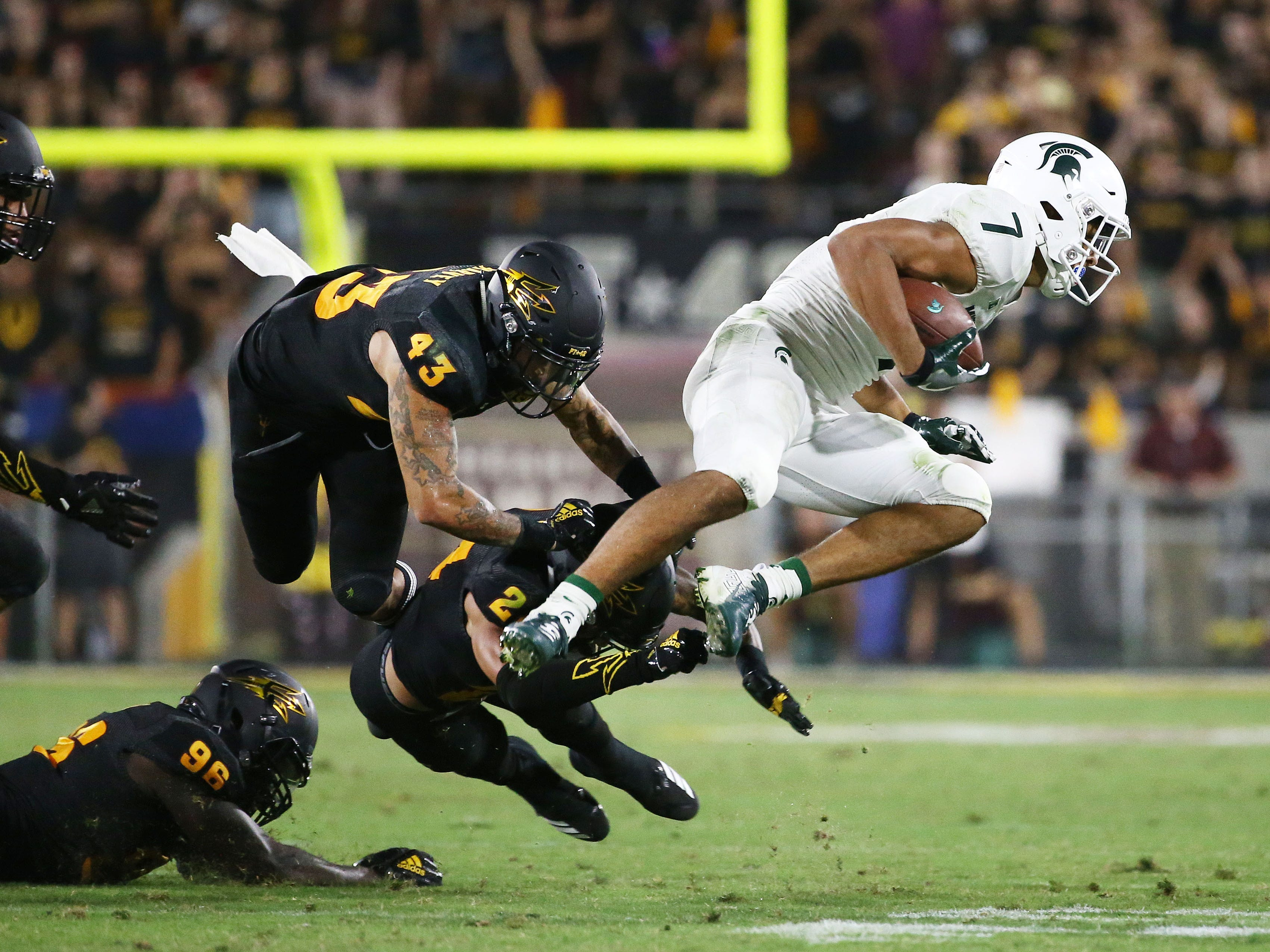 Arizona State's Jalen Harvey (43) and Chase Lucas (24) tackle Michigan State wide receiver Cody White in the second half on Sep. 8, 2018, at Sun Devil Stadium.