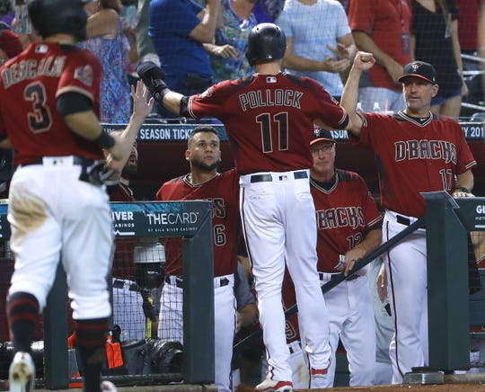 Diamondbacks AJ Pollock (11) celebrates with manager Torey Lovullo (R) after scoring during the sixth inning at Chase Field in Phoenix, Ariz. on Sept. 9, 2018.