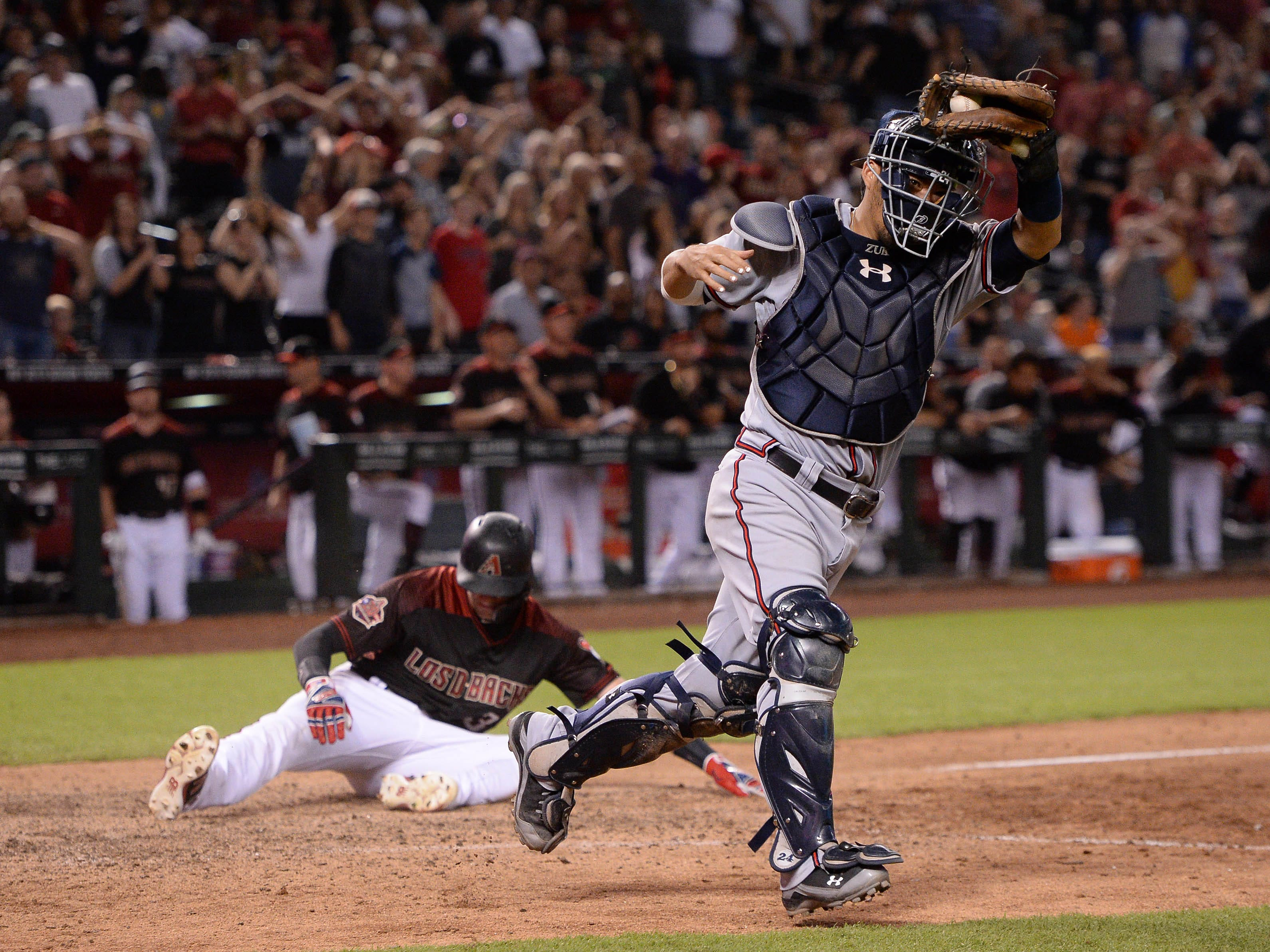 Sep 8, 2018; Phoenix, AZ, USA; Atlanta Braves catcher Kurt Suzuki (right) reacts after tagging out Arizona Diamondbacks shortstop Nick Ahmed (rear) at home to end the game at Chase Field. The Braves won 5-4. Mandatory Credit: Orlando Ramirez-USA TODAY Sports