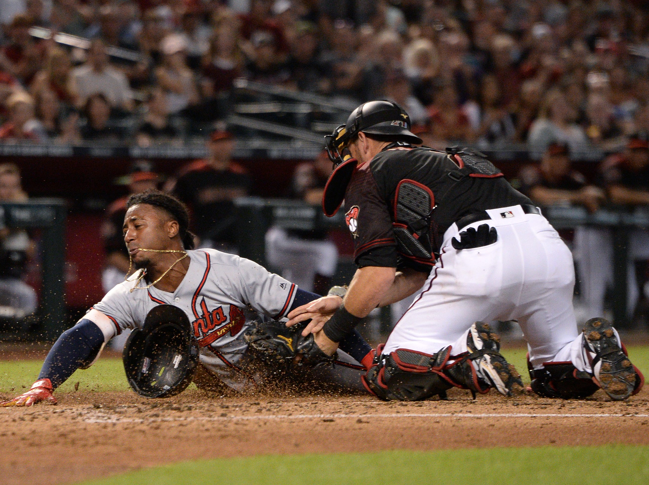 Sep 8, 2018; Phoenix, AZ, USA; Atlanta Braves second baseman Ozzie Albies (left) is tagged out at home by Arizona Diamondbacks catcher Jeff Mathis (right) during the second inning at Chase Field. Mandatory Credit: Orlando Ramirez-USA TODAY Sports