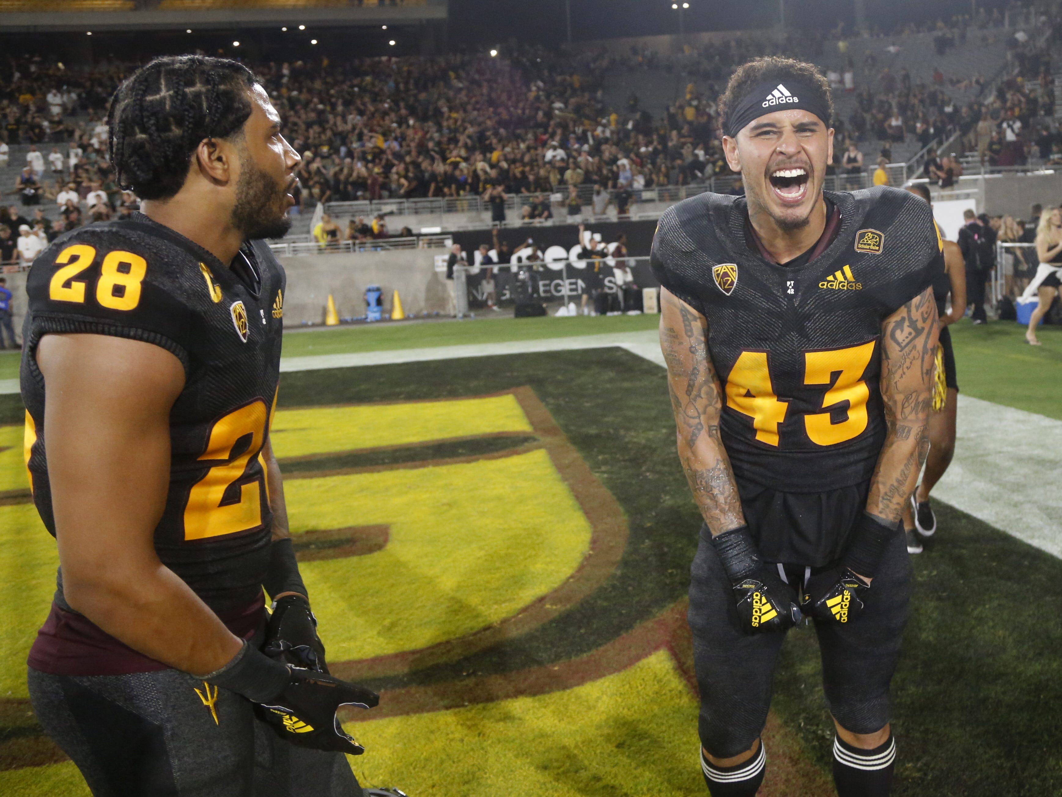 Arizona State Sun Devils defensive back Demonte King (28) and Arizona State Sun Devils safety Jalen Harvey (43) celebrate after defeating Michigan State 16-13 at Sun Devil Stadium in Tempe, Ariz. on Sept. 8, 2018.