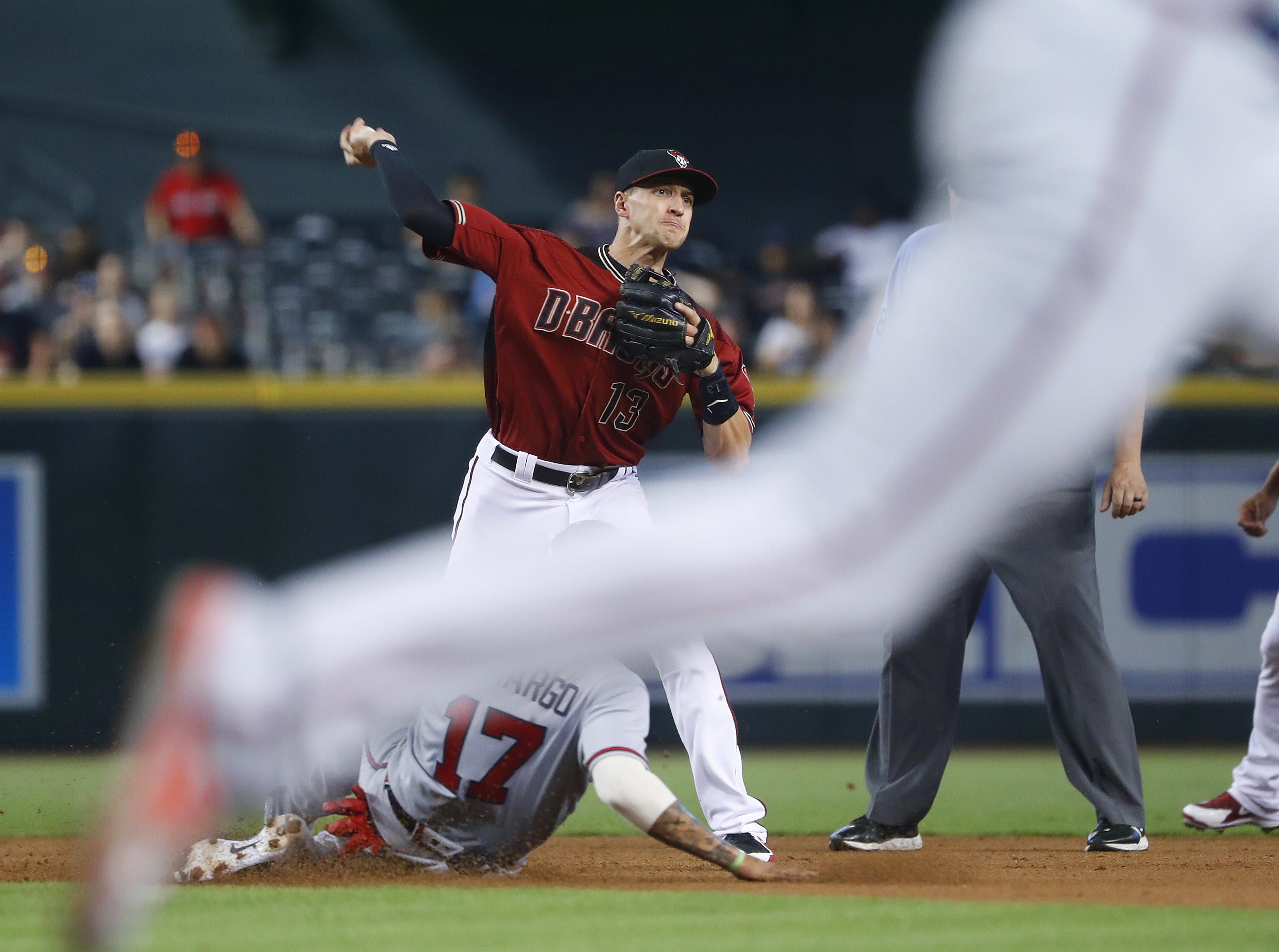 Diamondbacks Nick Ahmed (13) records a force out at second base on Braves Johan Camargo (17) and throws to first base for a double play during the fourth inning at Chase Field in Phoenix, Ariz. on Sept. 9, 2018.