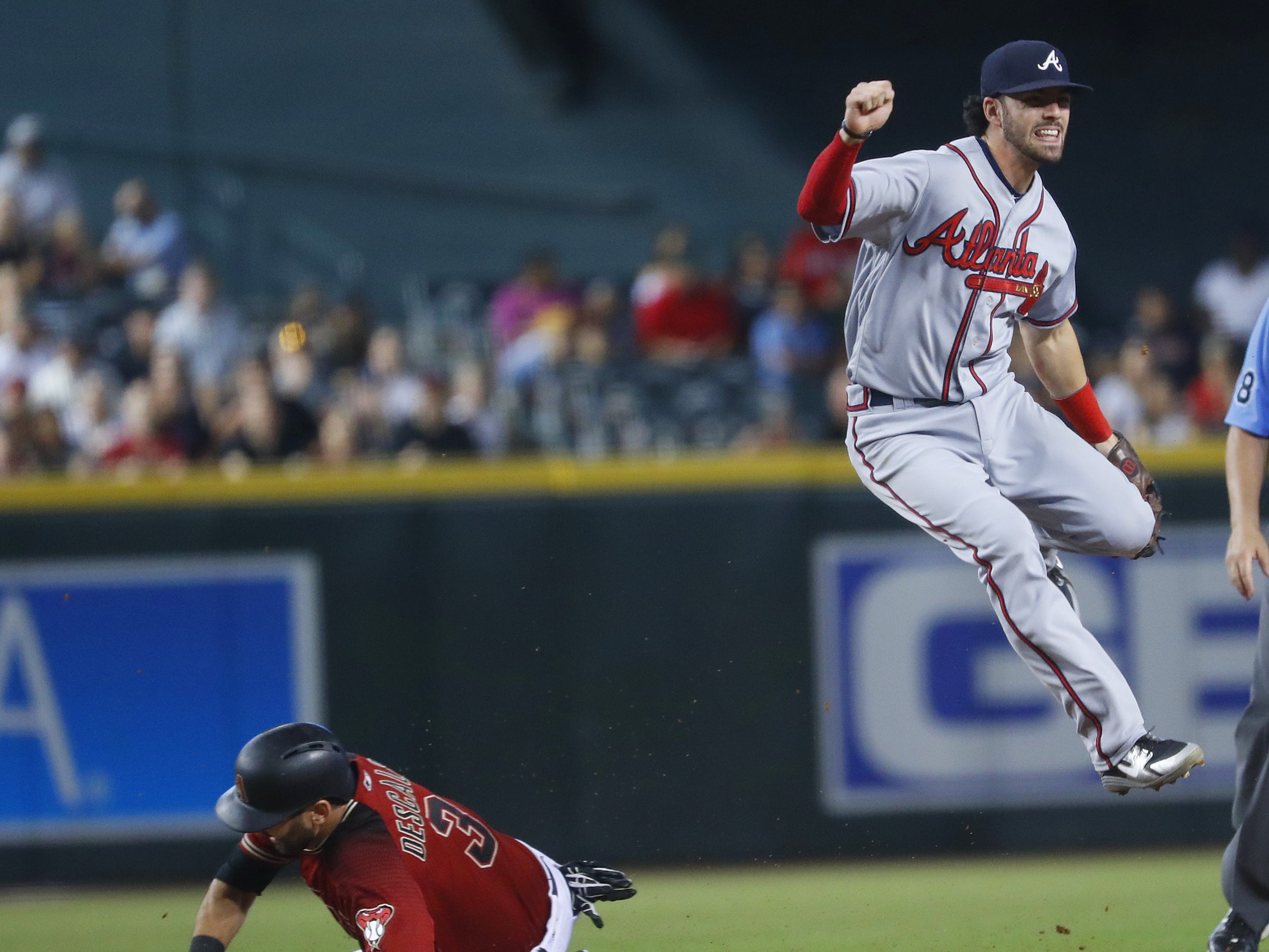 Braves Dansby Swanson (7) leaps over Diamondbacks Daniel Descalso (3) on a slide at second base during the sixth inning at Chase Field in Phoenix, Ariz. on Sept. 9, 2018.