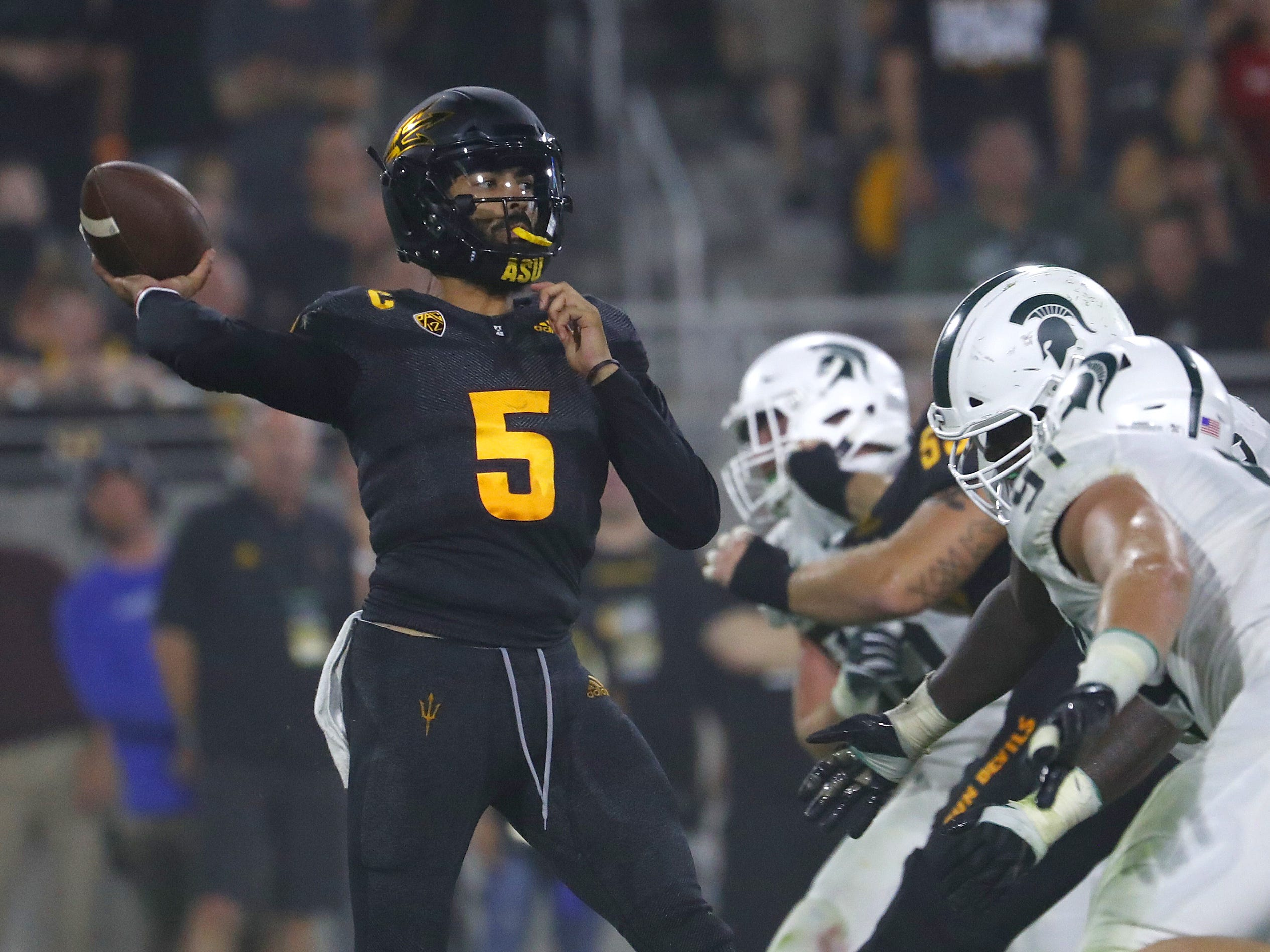 Arizona State Sun Devils quarterback Manny Wilkins (5) throws a pass under pressure from Michigan State during the second quarter at Sun Devil Stadium in Tempe, Ariz. on Sept. 8, 2018.