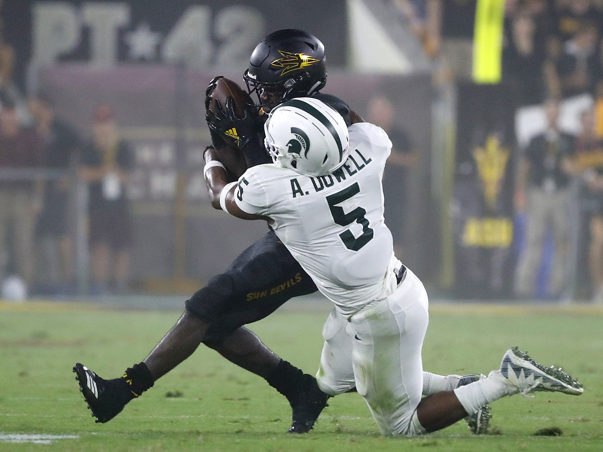 Michigan State's Andrew Dowell (5) tackles Arizona State Sun Devils running back Eno Benjamin (3) after a catch during the second quarter at Sun Devil Stadium in Tempe, Ariz. on Sept. 8, 2018.