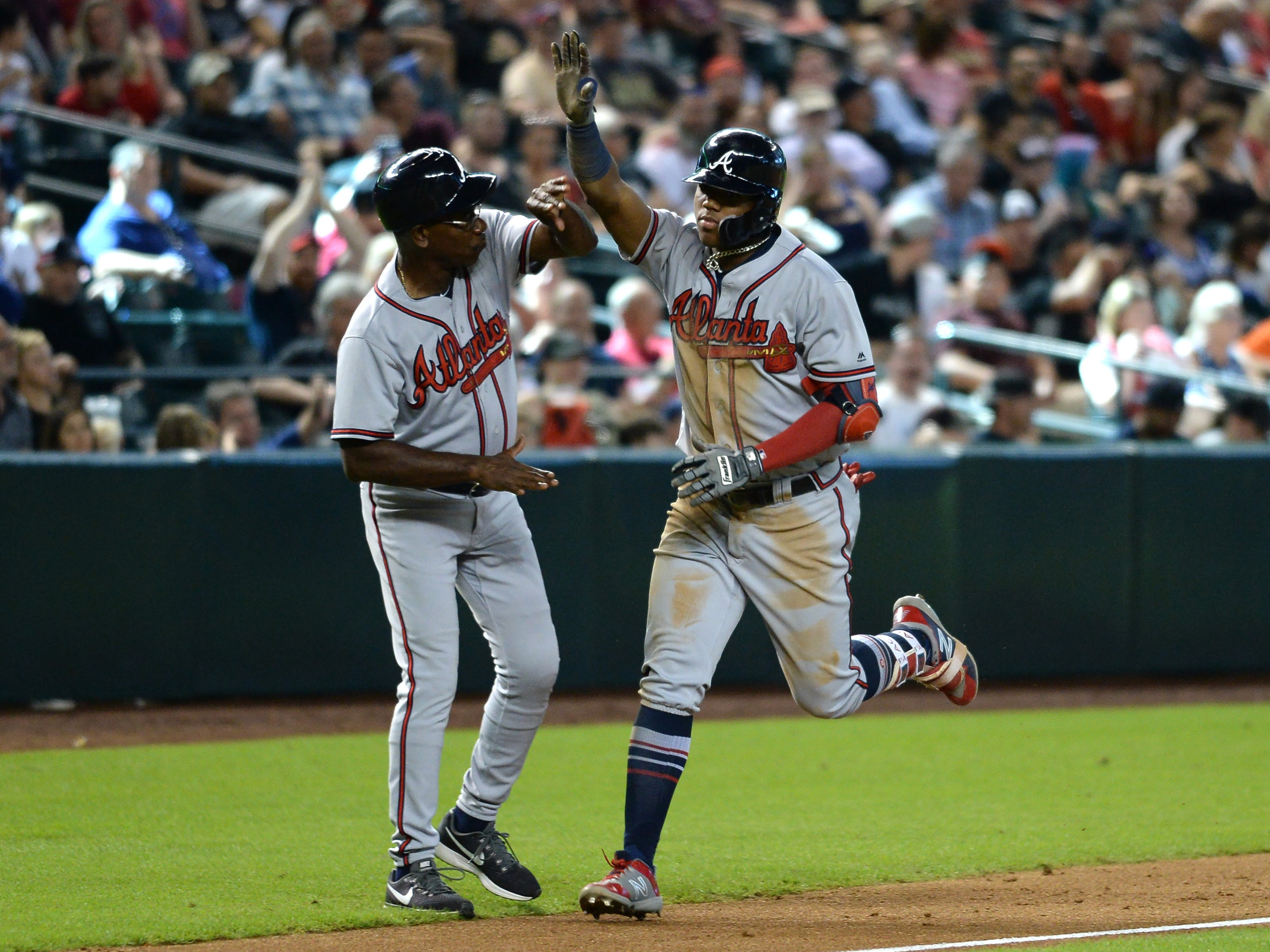 Sep 9, 2018; Phoenix, AZ, USA; Atlanta Braves left fielder Ronald Acuna Jr. (13) slaps hands with Atlanta Braves third base coach Ron Washington (37) after hitting a two-run home run against the Arizona Diamondbacks during the sixth inning at Chase Field.