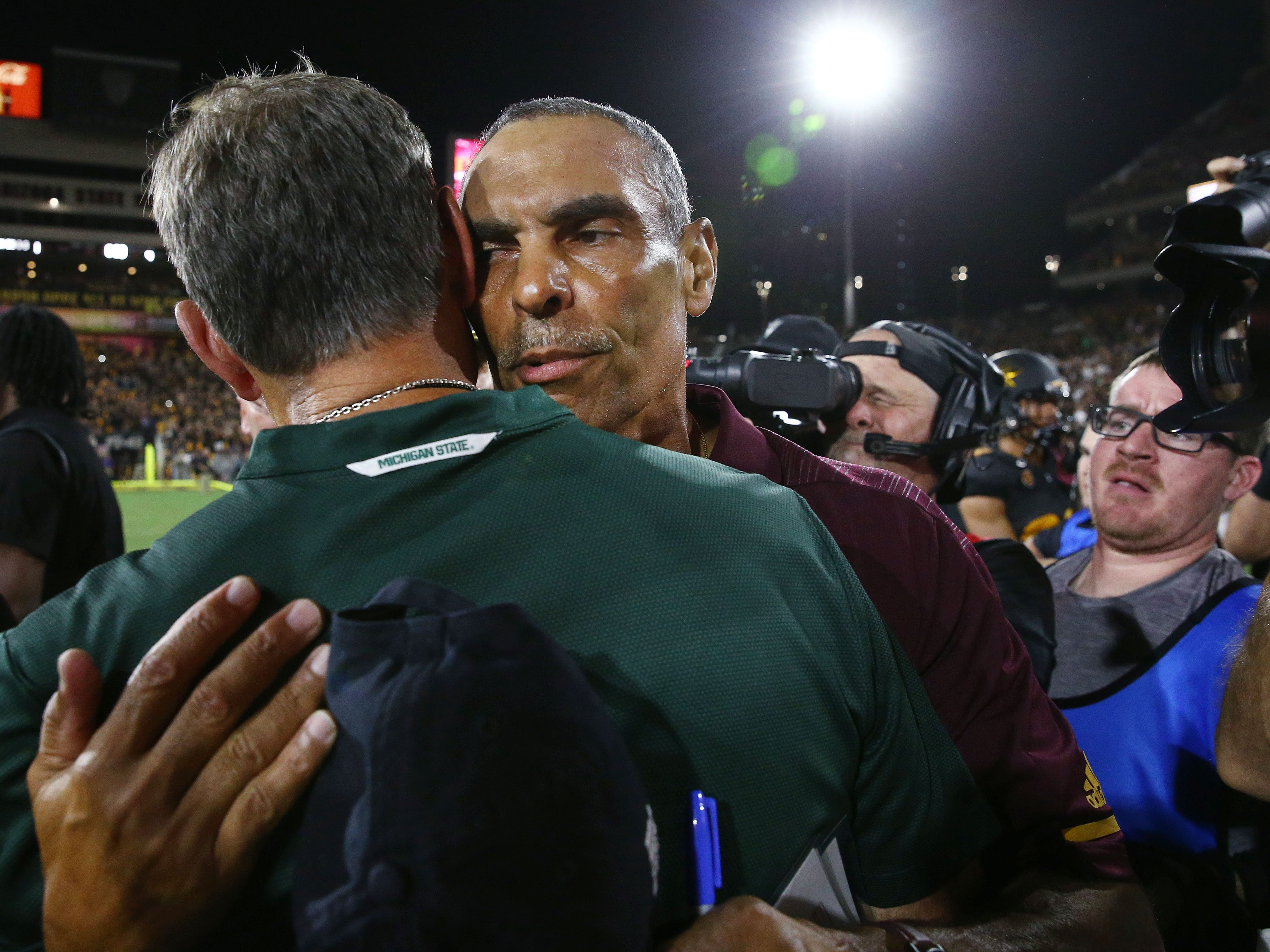 Arizona State head coach Herm Edwards hugs Michigan State head coach Mark Dantonio after the Sun Devils defeated Spartans 16-13 on Sep. 8, 2018, at Sun Devil Stadium.