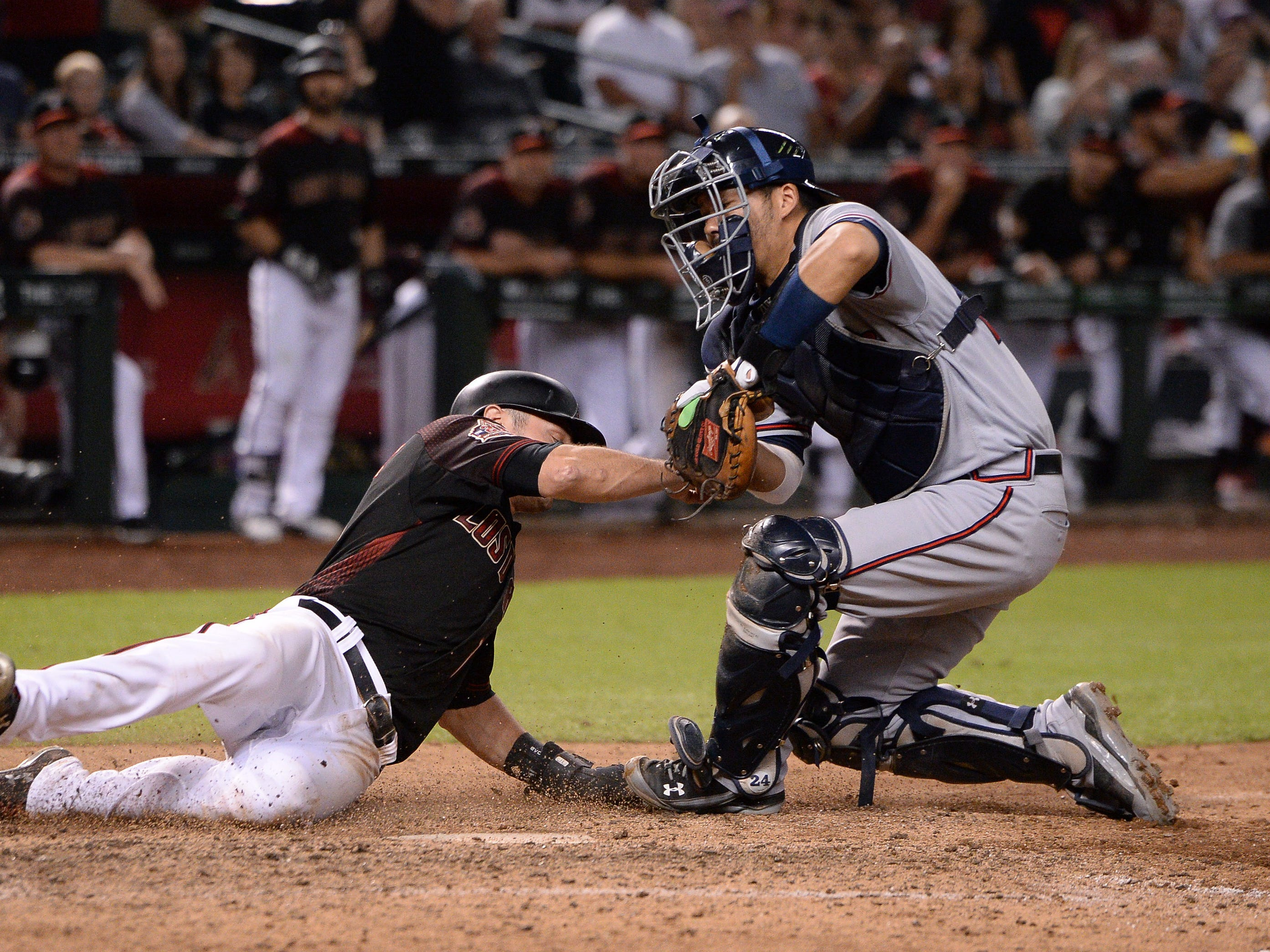 Sep 8, 2018; Phoenix, AZ, USA; Arizona Diamondbacks center fielder A.J. Pollock (left) is tagged out at home by Atlanta Braves catcher Kurt Suzuki (right) during the ninth inning at Chase Field. Mandatory Credit: Orlando Ramirez-USA TODAY Sports