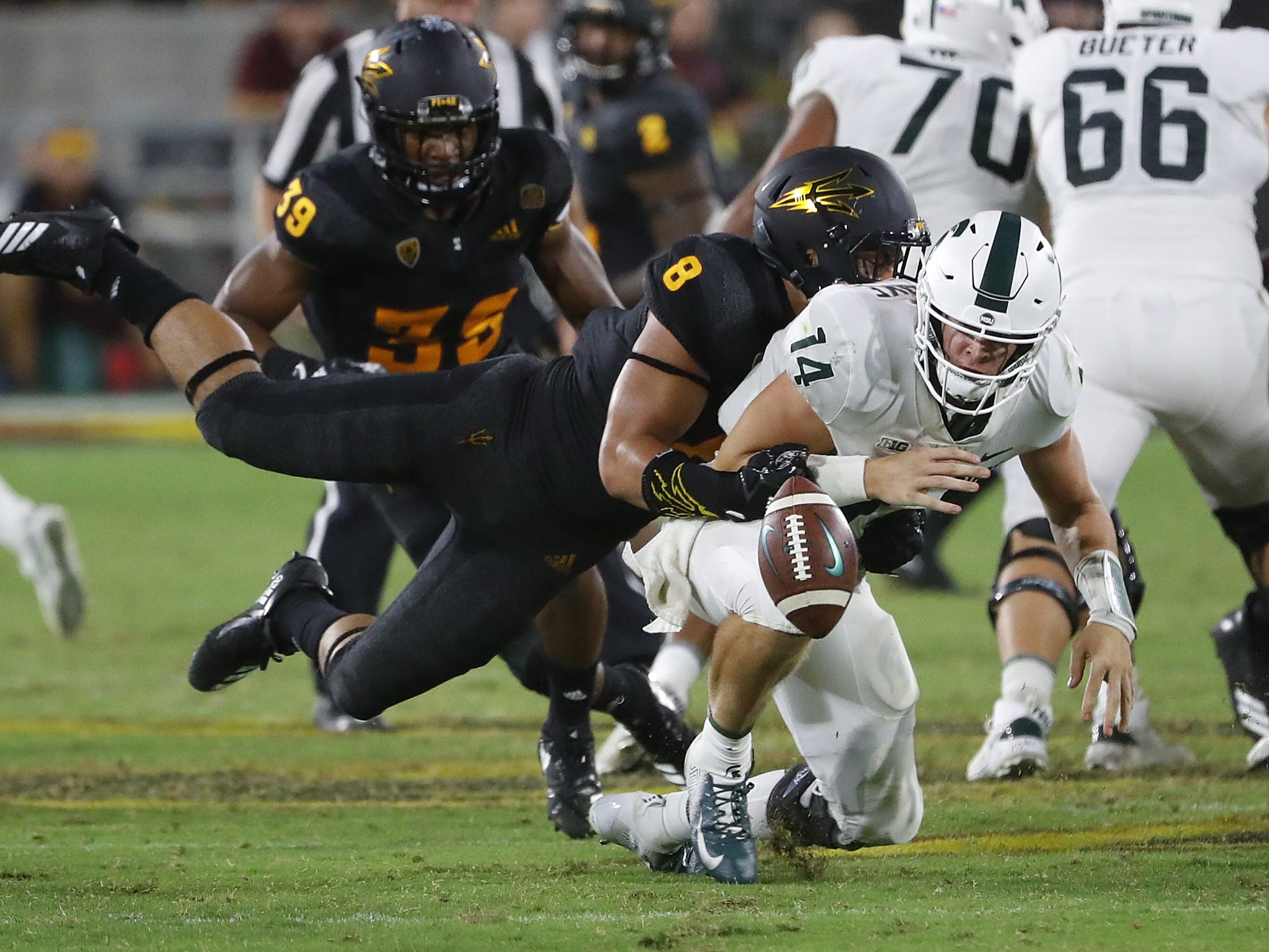 Arizona State Sun Devils linebacker Merlin Robertson (8) forces a fumble on a sack of Michigan State's quarterback Brian Lewerke (14) during the fourth quarter at Sun Devil Stadium in Tempe, Ariz. on Sept. 8, 2018.