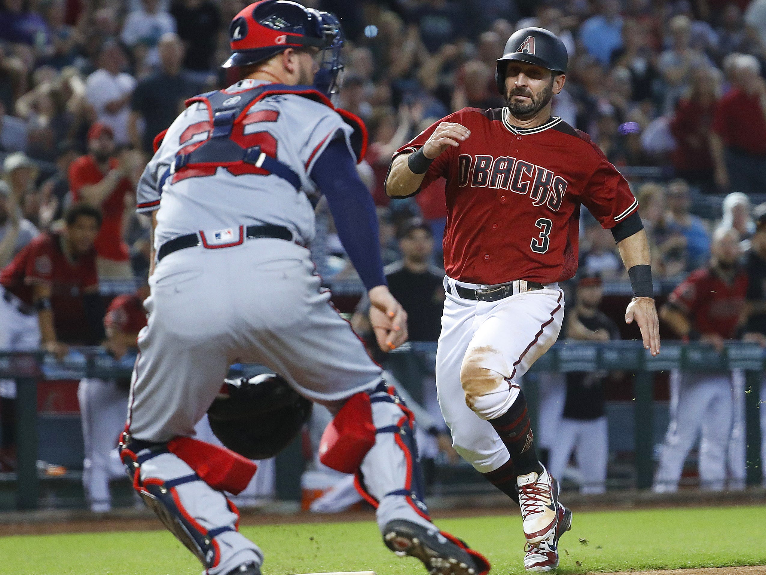 Diamondbacks Daniel Descalso (3) comes home against Braves catcher Tyler Flowers (25), scoring during the sixth inning at Chase Field in Phoenix, Ariz. on Sept. 9, 2018.
