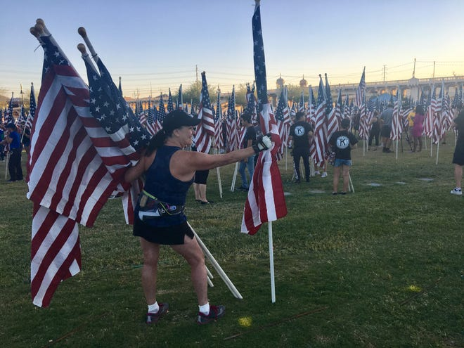 Debra Onken on the edge of the grass at Tempe Beach Park just after the sun came up on Sept. 8, 2018, holding eight American flags on poles. This was her fifth year helping set up the display.