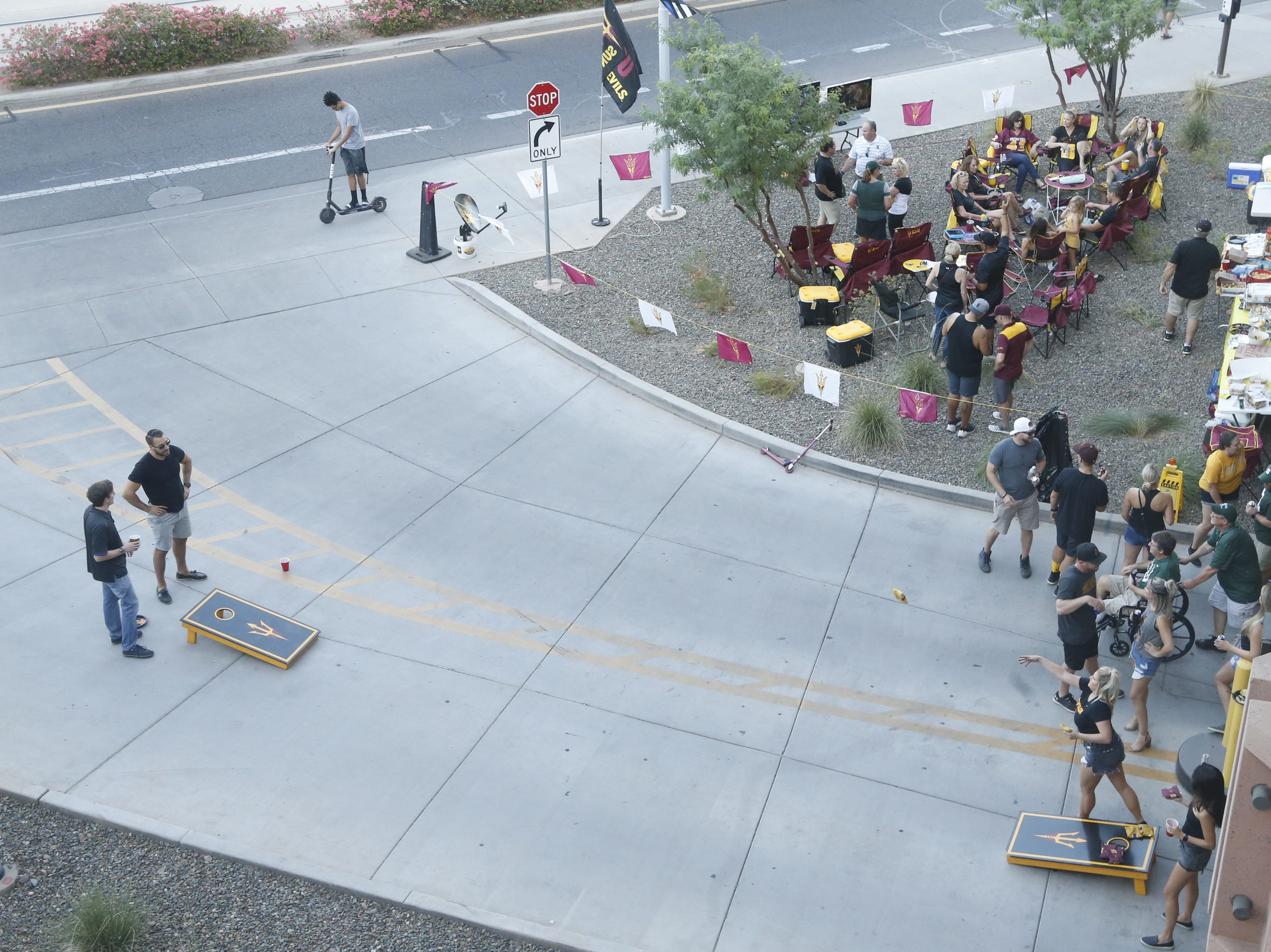 ASU fans stake their claims to empty exit lanes for games of corn hole before an ASU game against Michigan State at Sun Devil Stadium in Tempe, Ariz. on Sept. 8, 2018.