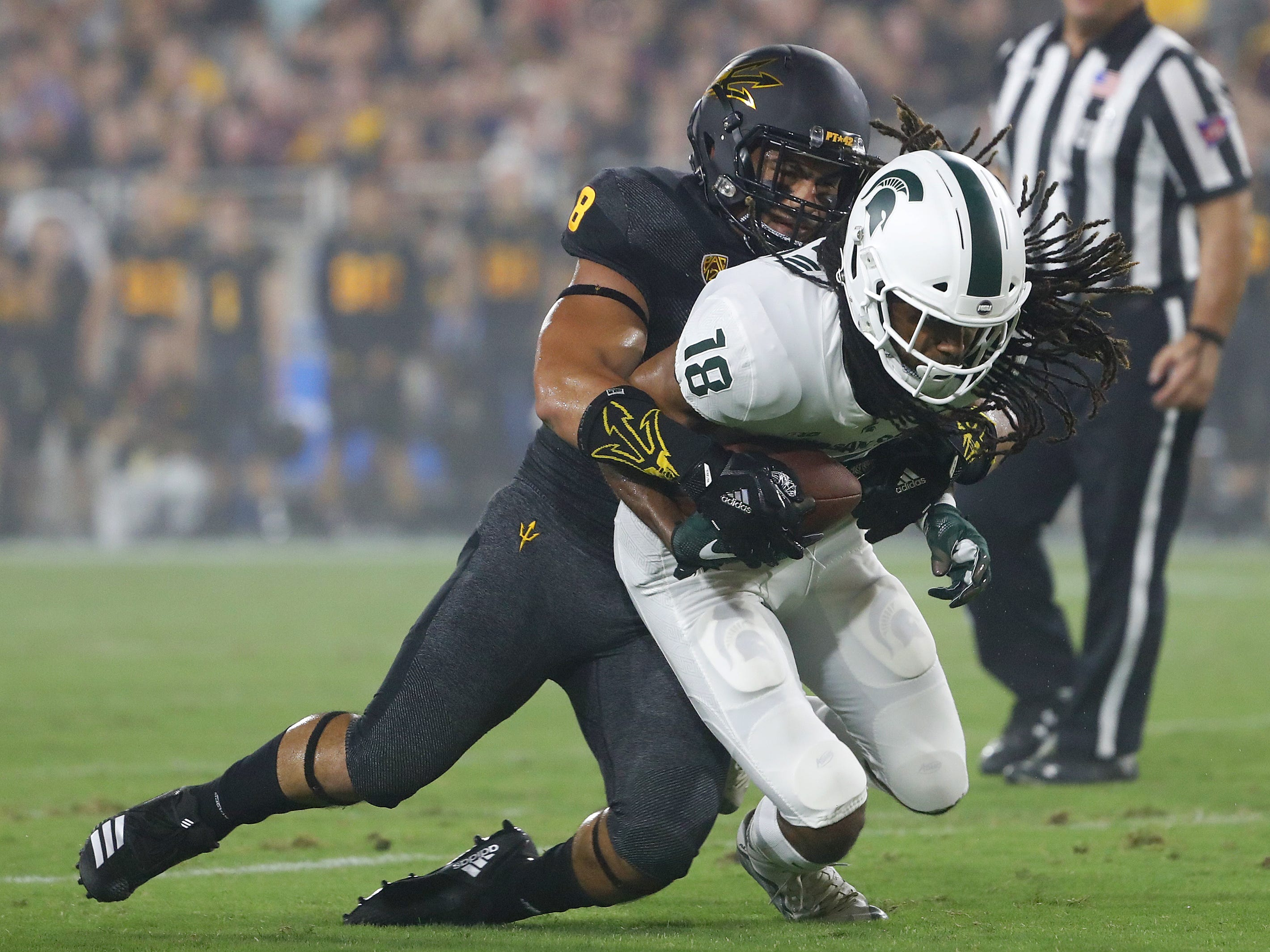 Arizona State Sun Devils linebacker Merlin Robertson (8) tackles Michigan State's Felton Davis III (18) after he makes a catch during the second quarter at Sun Devil Stadium in Tempe, Ariz. on Sept. 8, 2018.