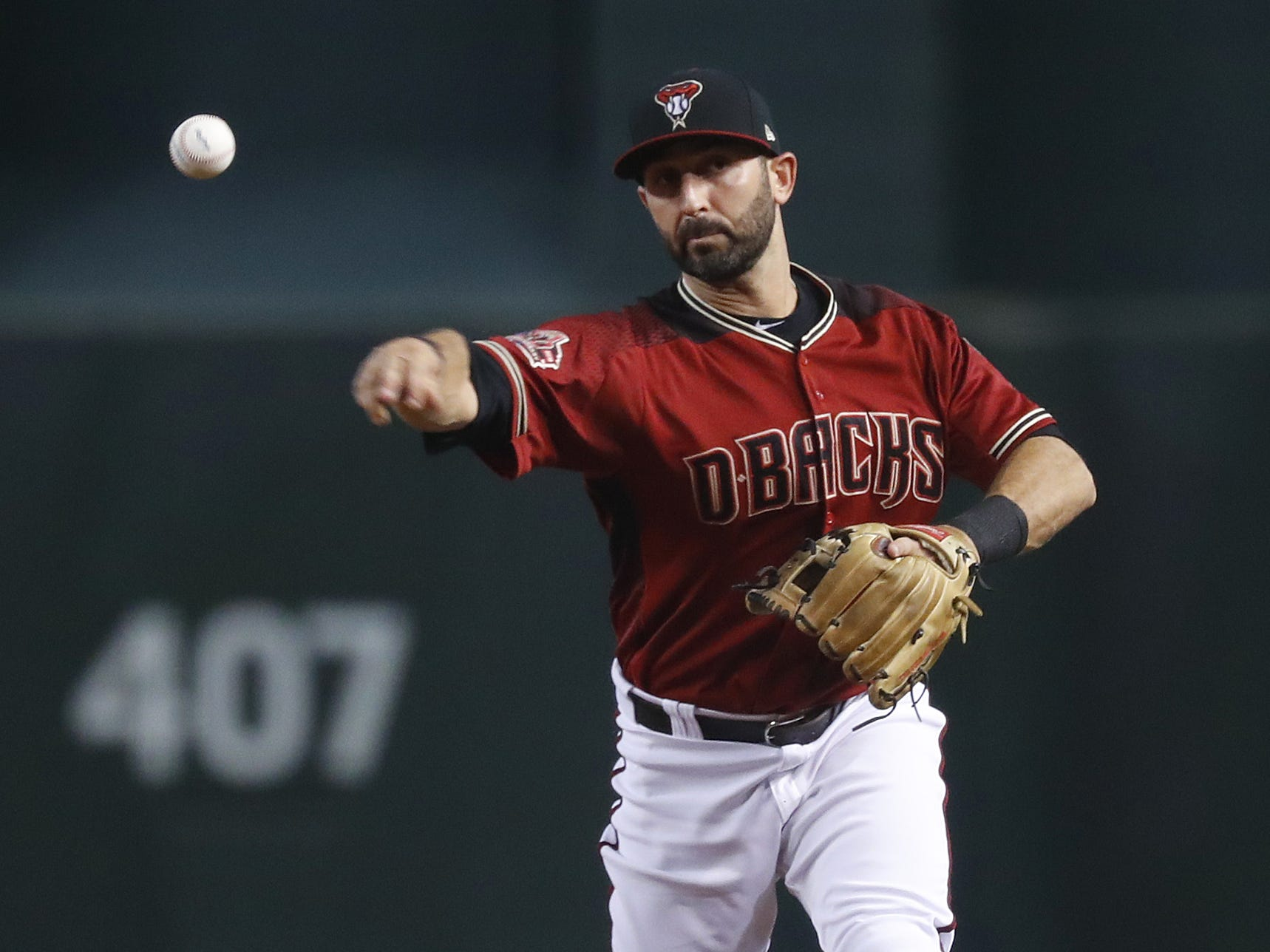Diamondbacks Daniel Descalso throws out a Braves runner at first base during the third inning at Chase Field in Phoenix, Ariz. on Sept. 9, 2018.