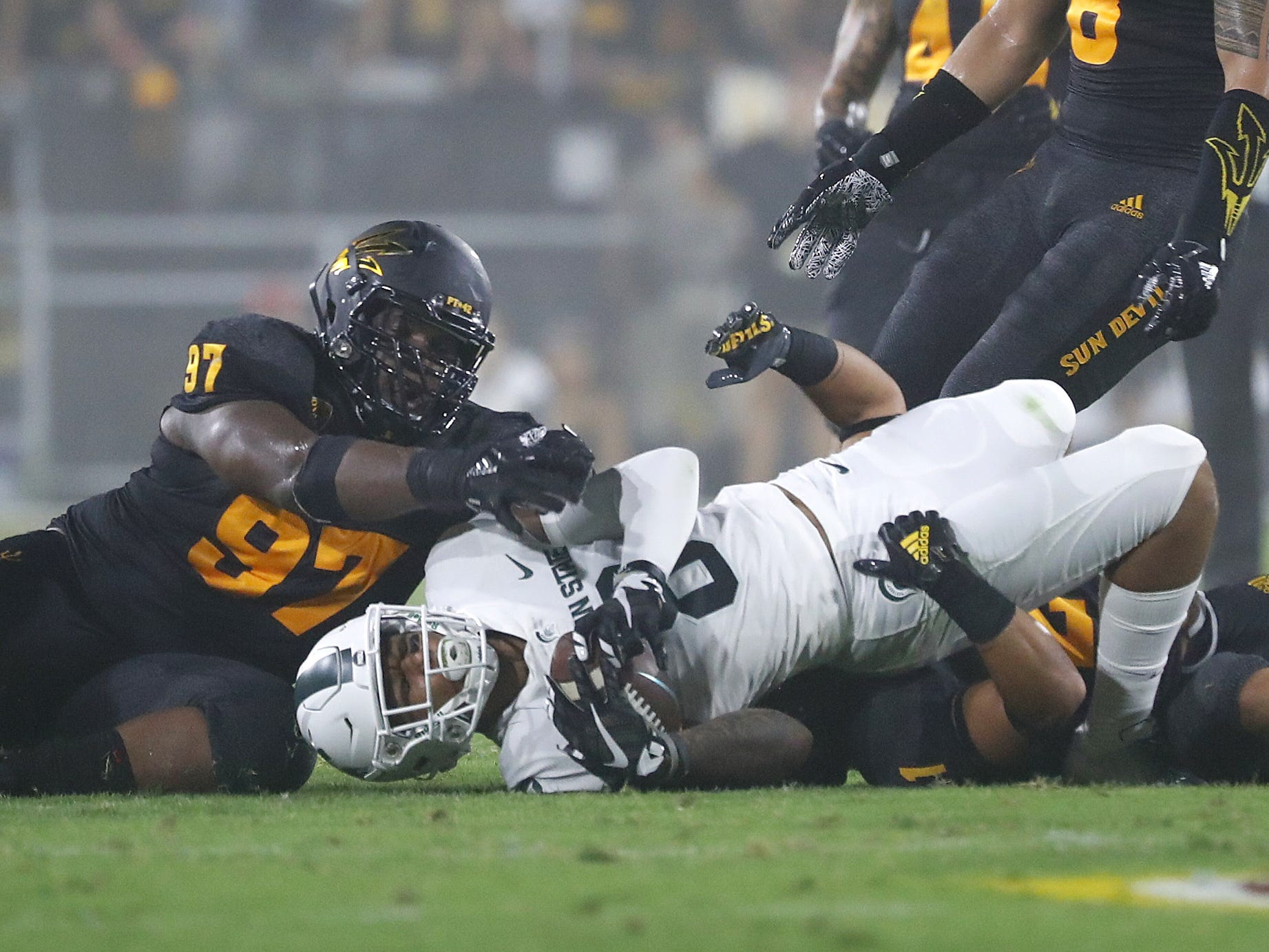 Arizona State University defenders tackle Michigan State's Jalen Nailor (8) during the second quarter at Sun Devil Stadium in Tempe, Ariz. on Sept. 8, 2018.