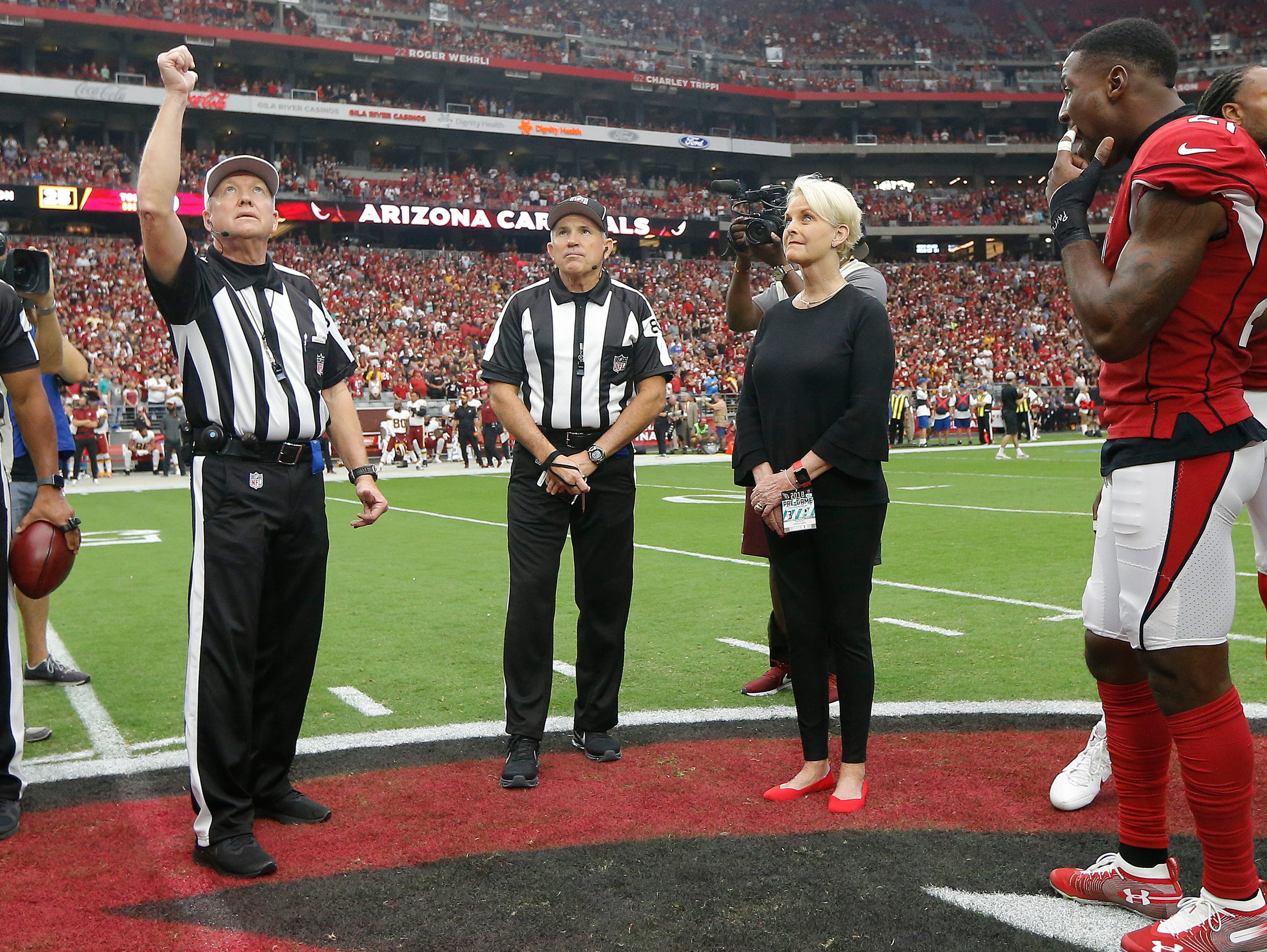 Cindy McCain, wife of the late U.S. Sen. John McCain, R-Ariz., stands with Arizona Cardinals and Washington Redskins players as an honorary team captain during the coin toss by referee Walt Coleman, left, prior to an NFL football game , Sept. 9, 2018, in Glendale, Ariz.