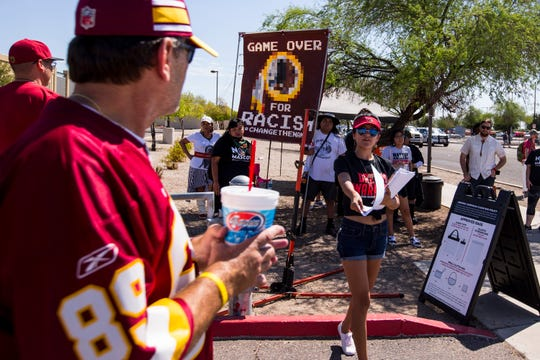 Savanna Castorena gives out flyers to Redskins fans during a protest against Washington's mascot before the Cardinals game against the Redskins Sept. 9, 2018, at State Farm Stadium in Glendale.