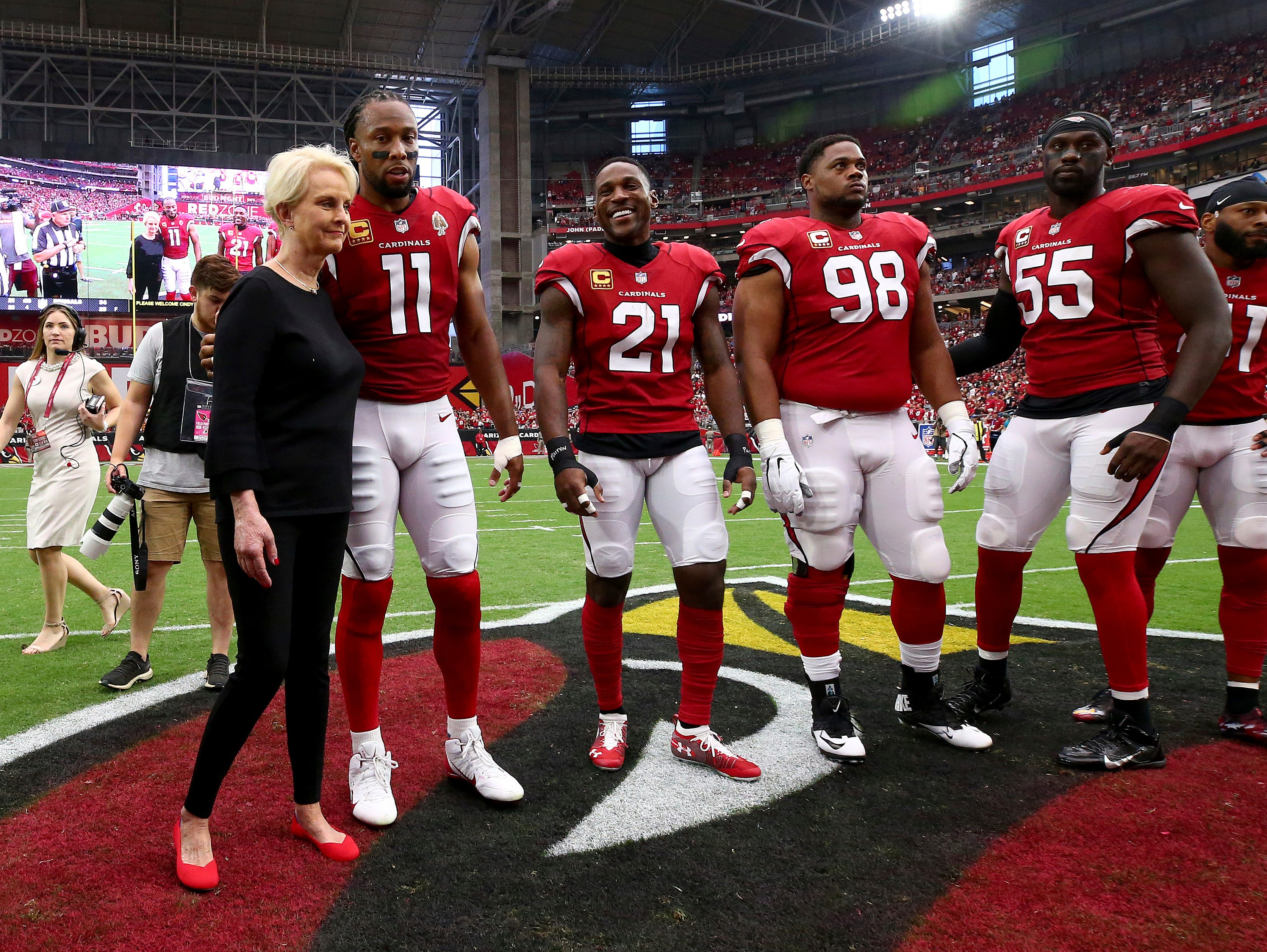 Cindy McCain, wife of the late U.S. Sen. John McCain, R-Ariz., embraces Arizona Cardinals' Larry Fitzgerald (11), Patrick Peterson (21), Corey Peters (98) and Chandler Jones (55) as an honorary team captain during the coin toss prior to an NFL football game against the Washington Redskins , Sunday, Sept. 9, 2018, in Glendale, Ariz. (AP Photo/Rob Schumacher, Pool)