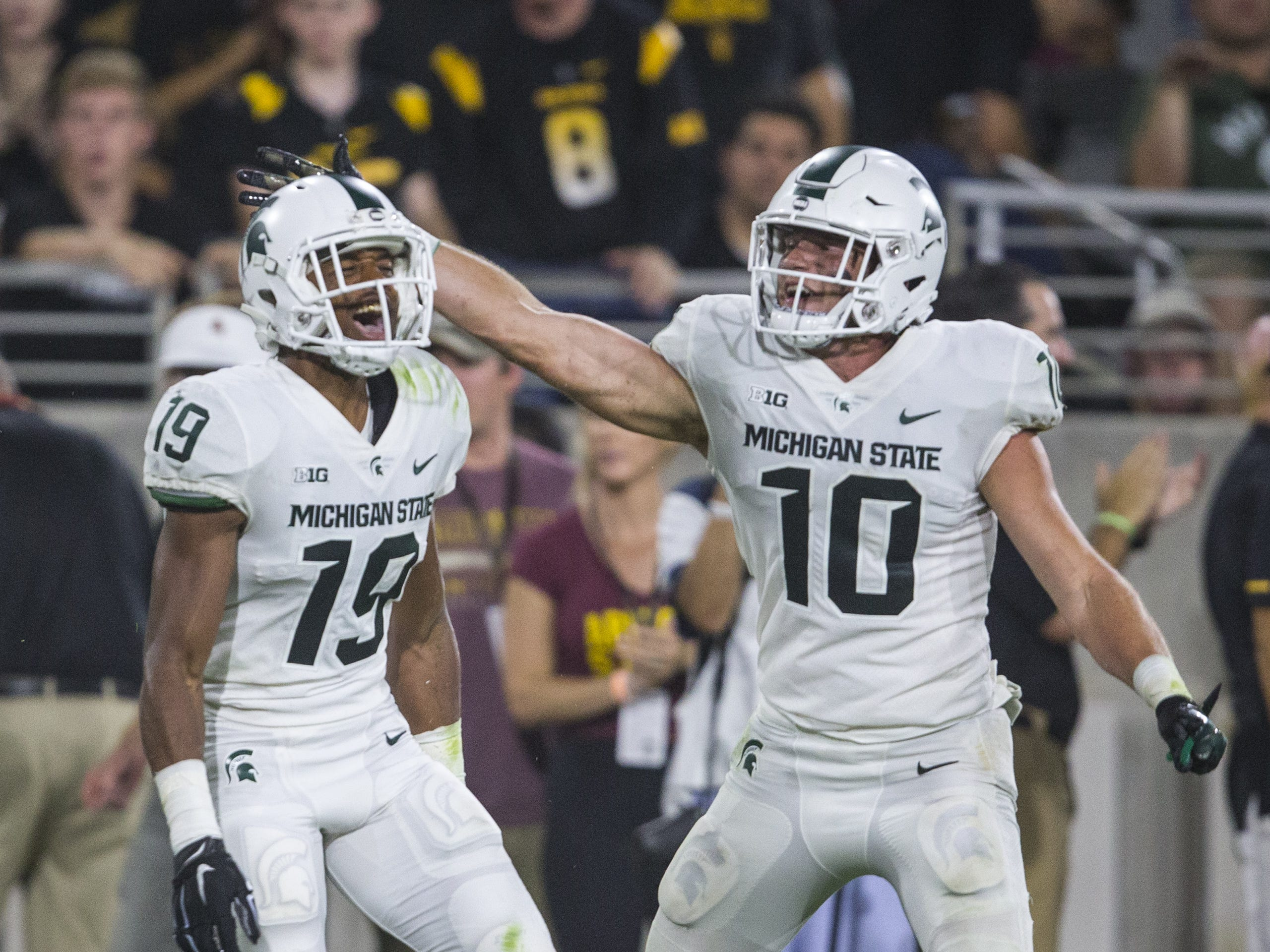 Michigan State's Josh Butler (19) and Matt Morrissey (10) celebrate after Butler broke up a catch against Arizona State in the 3rd quarter on Saturday, Sept. 8, 2018, at Sun Devil Stadium in Tempe, Ariz.