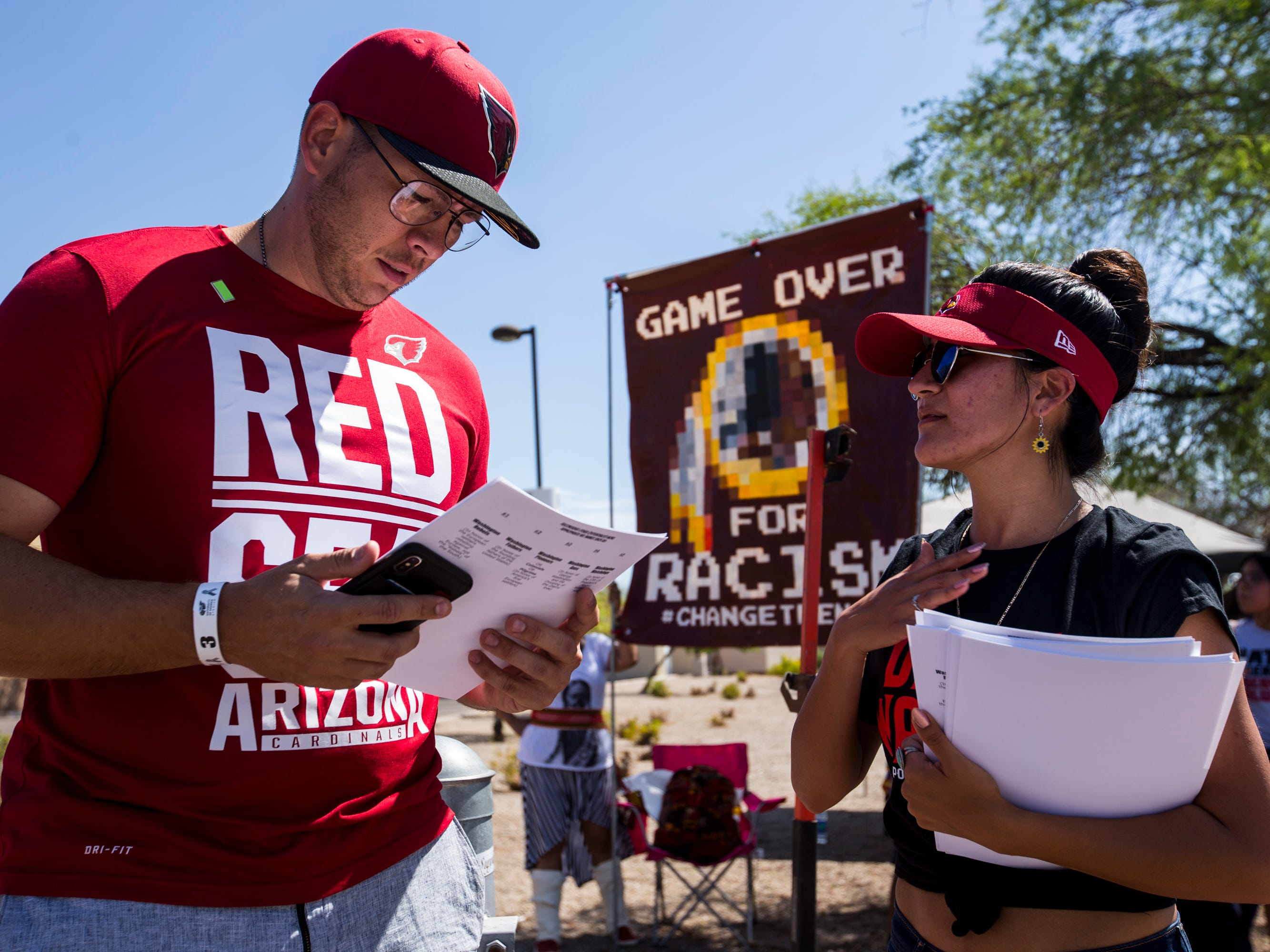 Savanna Castorena gives flyers to a Cardinals fan during a protest against Washington's mascot before the Cardinals game against the Redskins Sept. 9, 2018, at State Farm Stadium in Glendale.