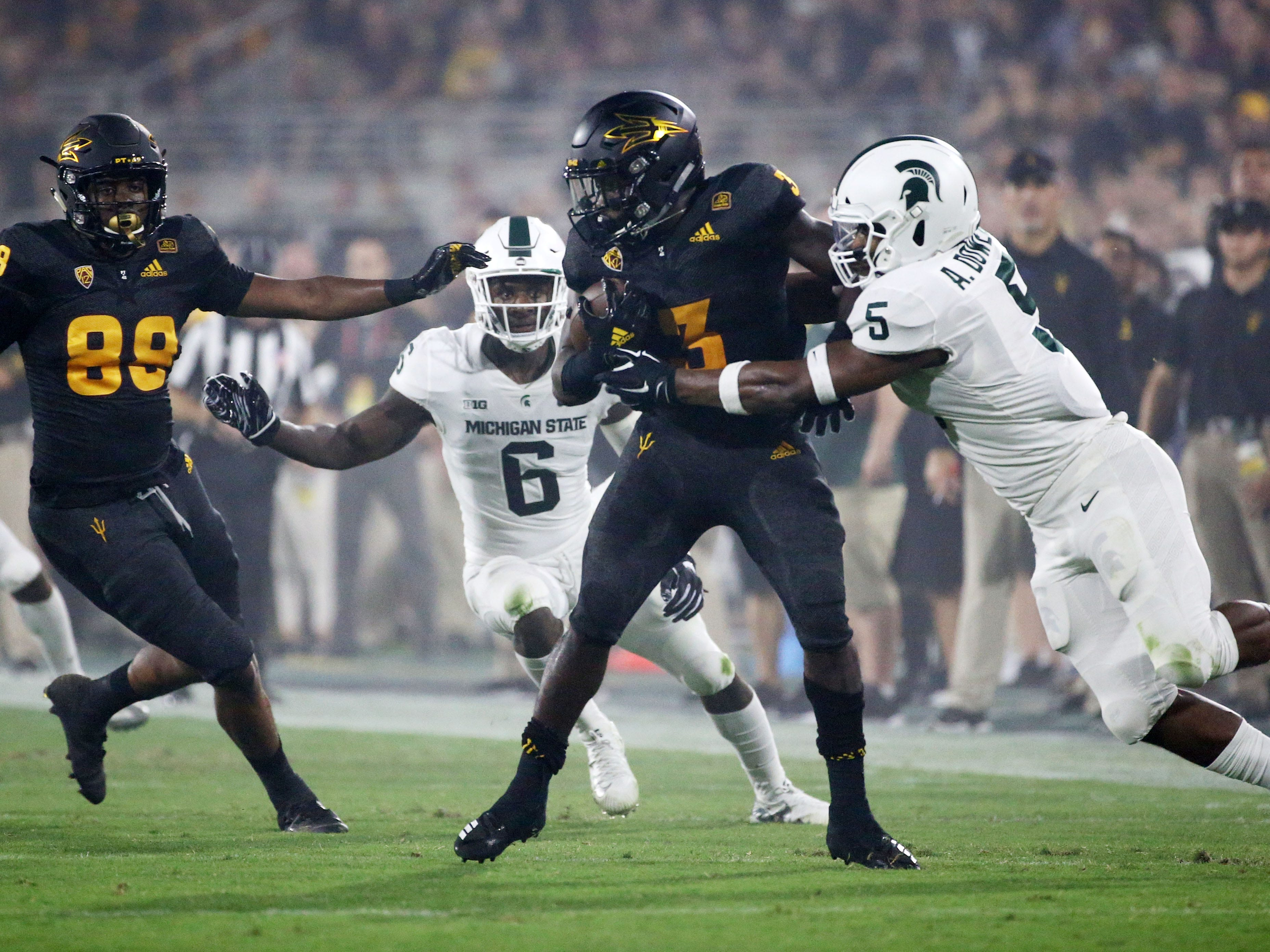 Arizona State running back Eno Benjamin is tackled by Michigan State linebacker Andrew Dowell defense on Sep. 8, 2018, at Sun Devil Stadium.