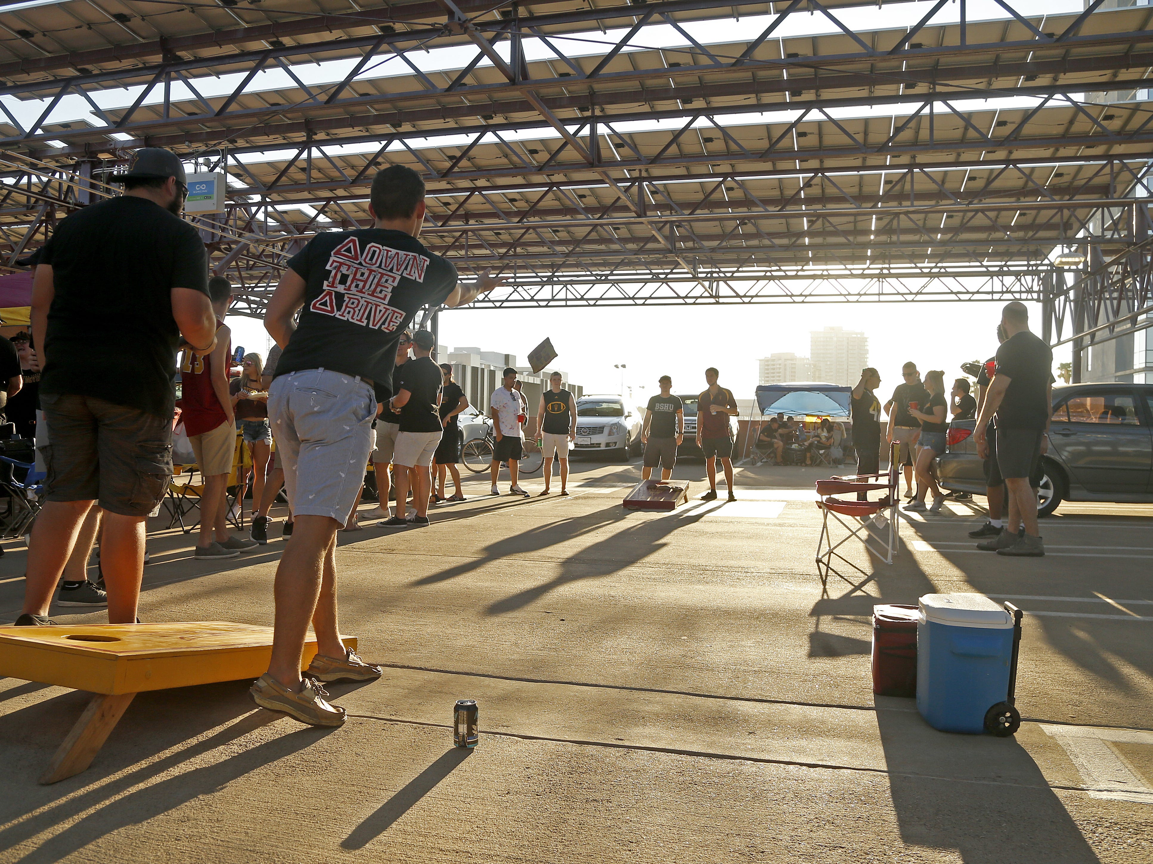 ASU students play bags on the top of a parking garage before an ASU game against Michigan State at Sun Devil Stadium in Tempe, Ariz. on Sept. 8, 2018.