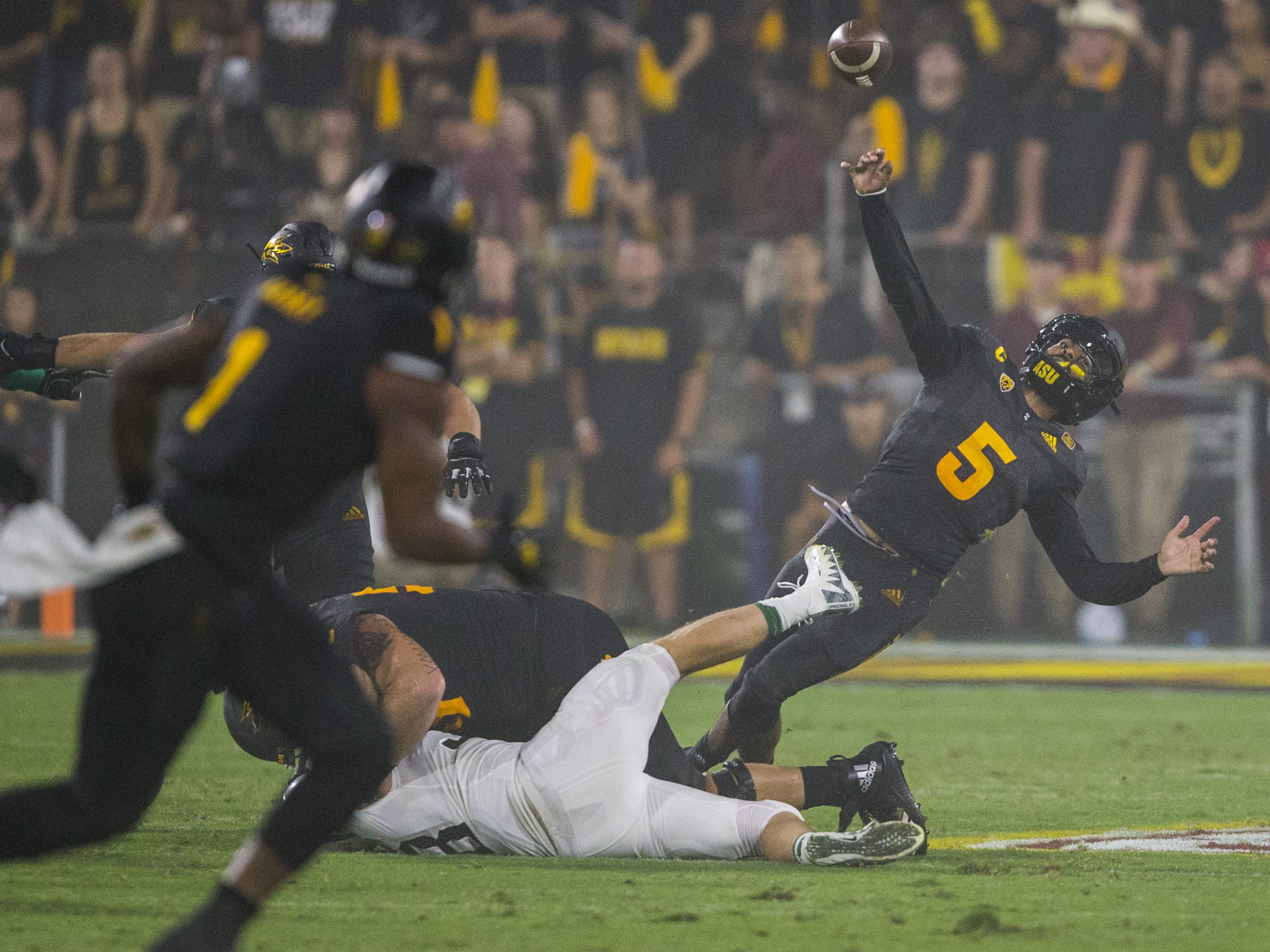 Arizona State's Manny Wilkins throws while being tripped against Michigan State in the 2nd quarter on Saturday, Sept. 8, 2018, at Sun Devil Stadium in Tempe, Ariz.