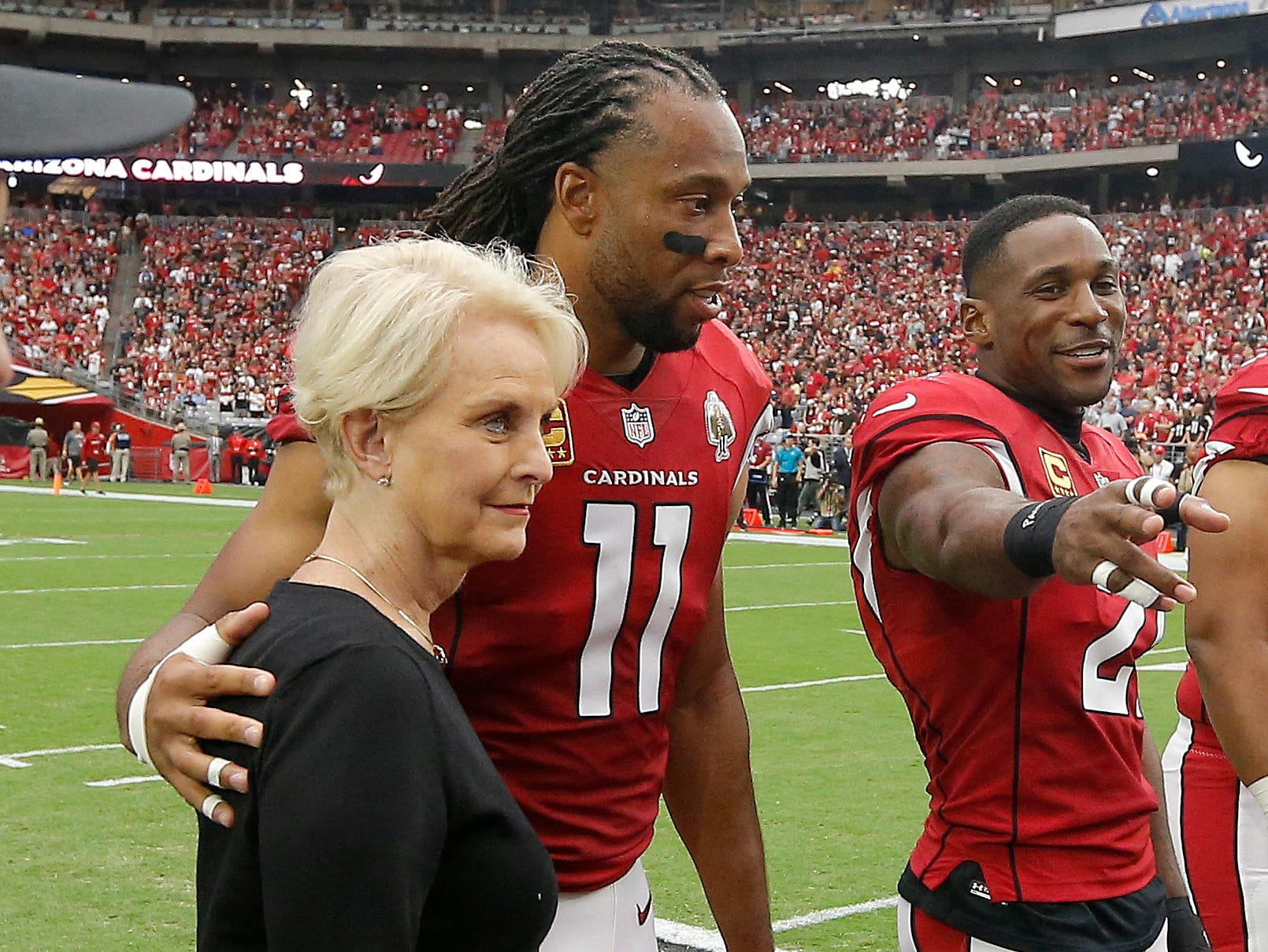 Cindy McCain, wife of the late U.S. Sen. John McCain, R-Ariz., stands with Arizona Cardinals wide receiver Larry Fitzgerald (11) as an honorary team captain during the coin toss prior to an NFL football game against the Washington Redskins, Sept. 9, 2018, in Glendale, Ariz.