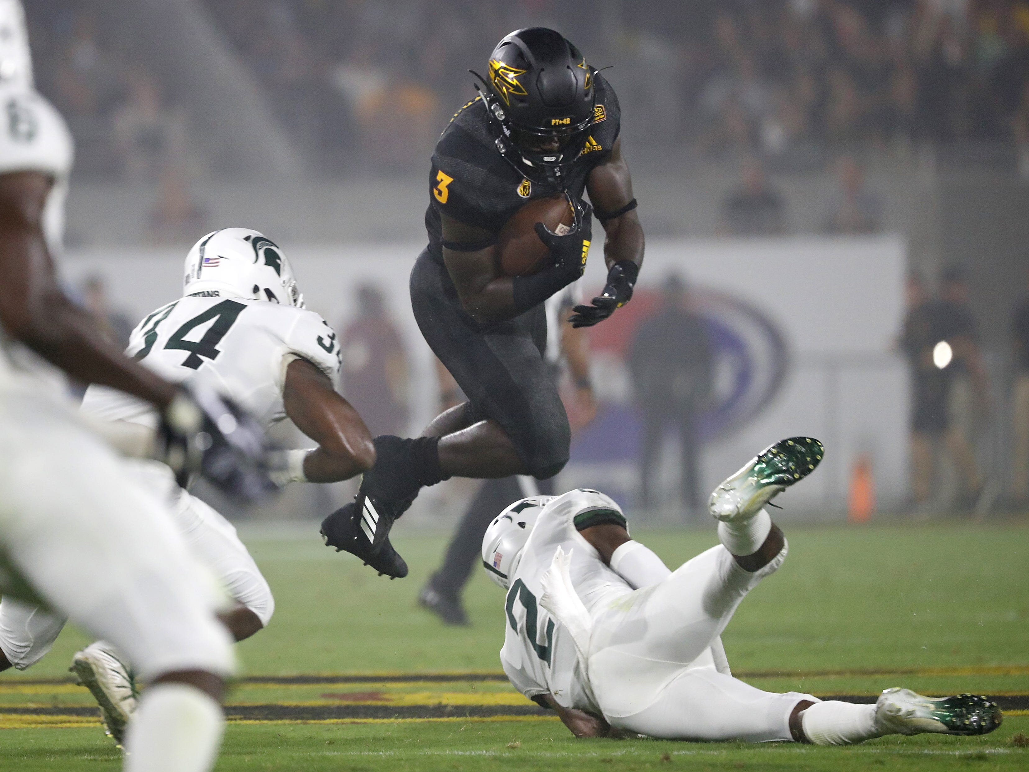 Arizona State Sun Devils running back Eno Benjamin (3) tries to hurdle a tackle from Michigan Justin Layne (2) during the first quarter at Sun Devil Stadium in Tempe, Ariz. on Sept. 8, 2018.