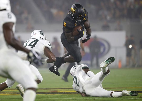 Arizona State Sun Devils running back Eno Benjamin (3) tries to hurdle tackle attempts from Michigan State's Antjuan Simmons (34) and Justin Layne (2) during the first quarter at Sun Devil Stadium in Tempe, Ariz. on Sept. 8, 2018.
