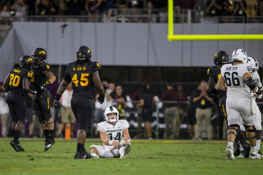 Brian Lewerke lies on the ground after being sacked against Arizona State in the fourth quarter last season.