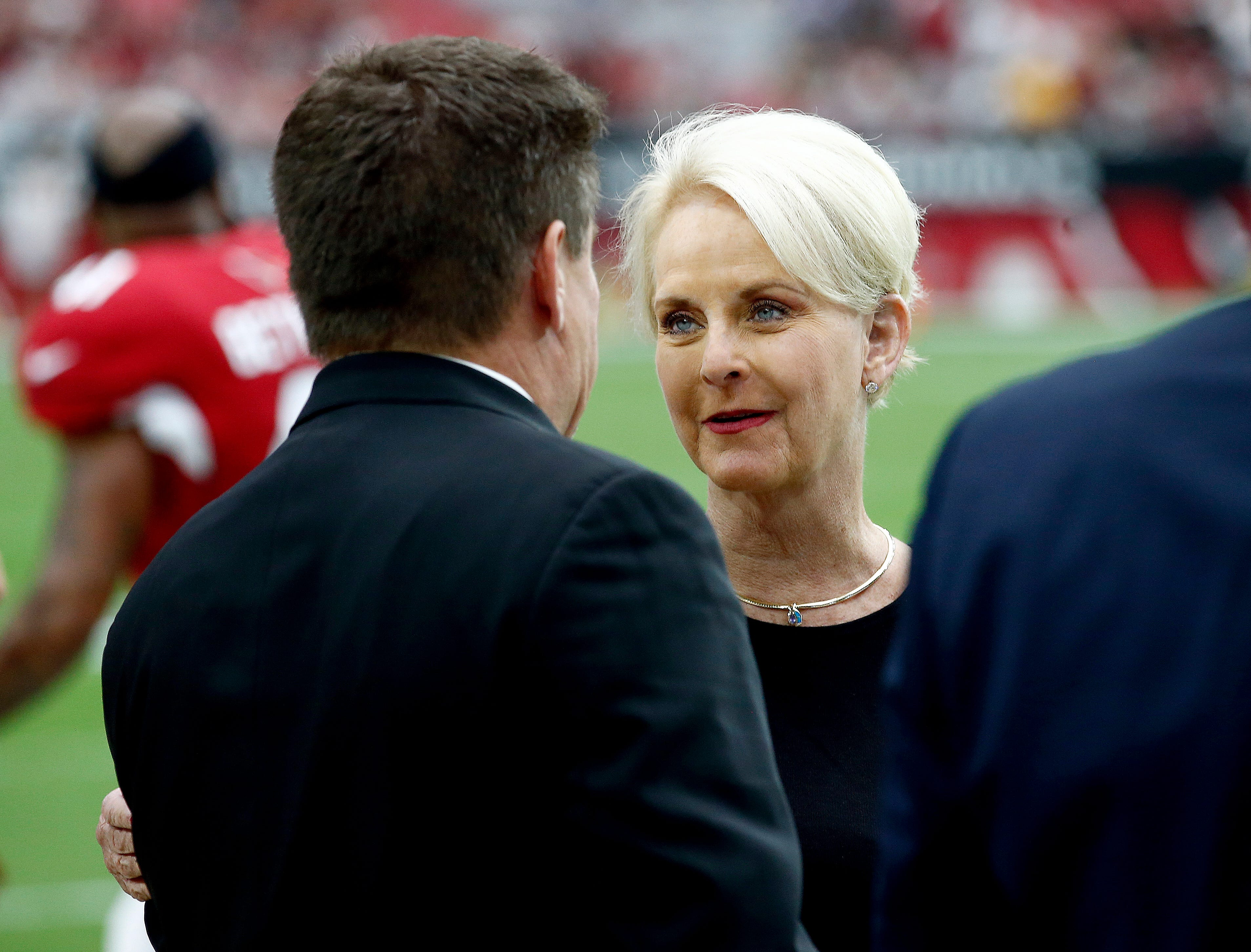 Cindy McCain, wife of the late U.S. Sen. John McCain, talks with Arizona Cardinals president Michael Bidwill prior to an NFL football game between the Washington Redskins and the Arizona Cardinals, Sept. 9, 2018, in Glendale, Ariz.