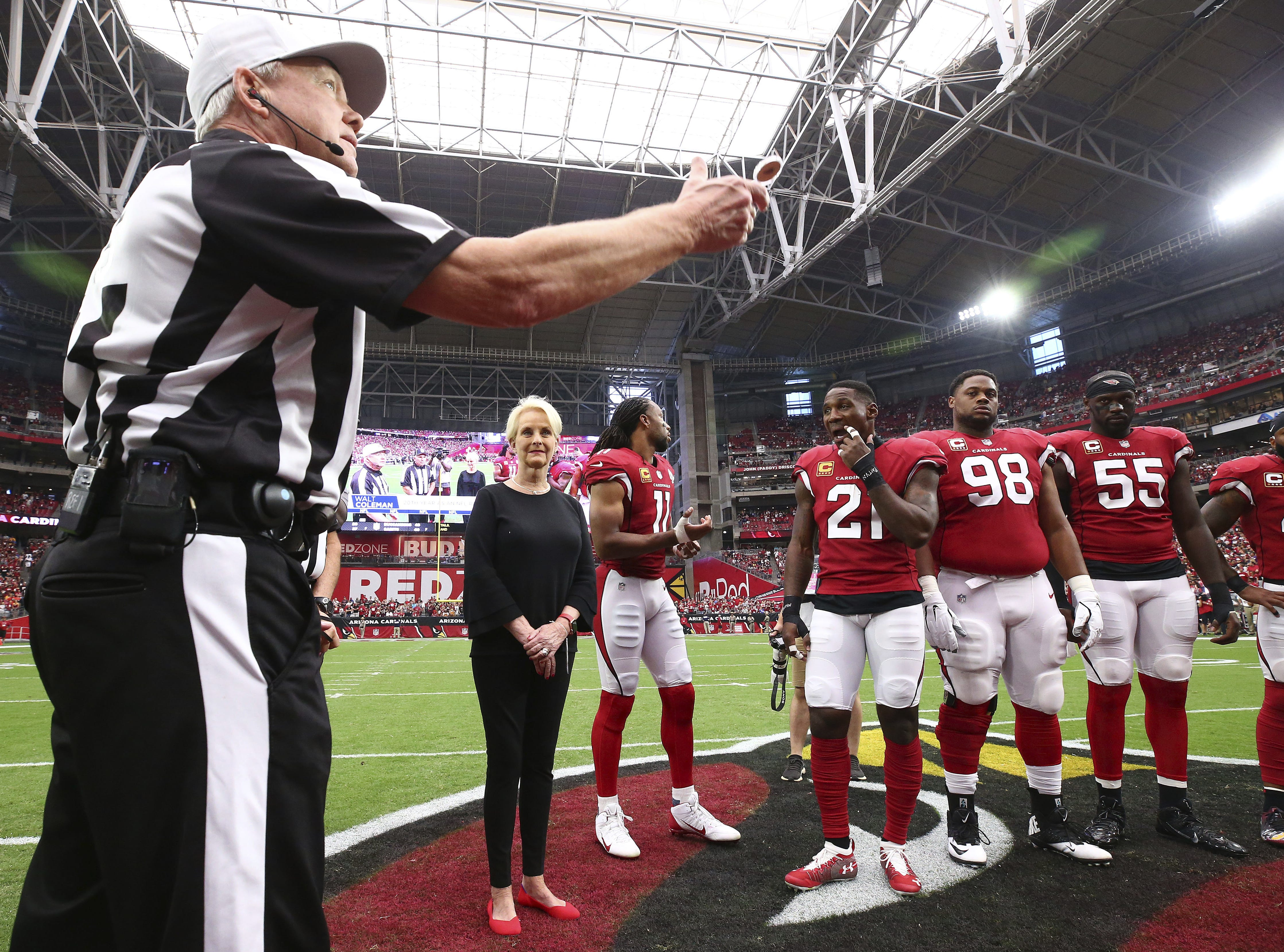 Cindy McCain, wife of the late U.S. Sen. John McCain stands with Arizona Cardinals' Larry Fitzgerald (11), Patrick Peterson (21), Corey Peters (98) and Chandler Jones (55) as an honorary team captain as referee Walt Coleman tosses the coin prior to an NFL football game against the Washington Redskins, Sept. 9, 2018, in Glendale.