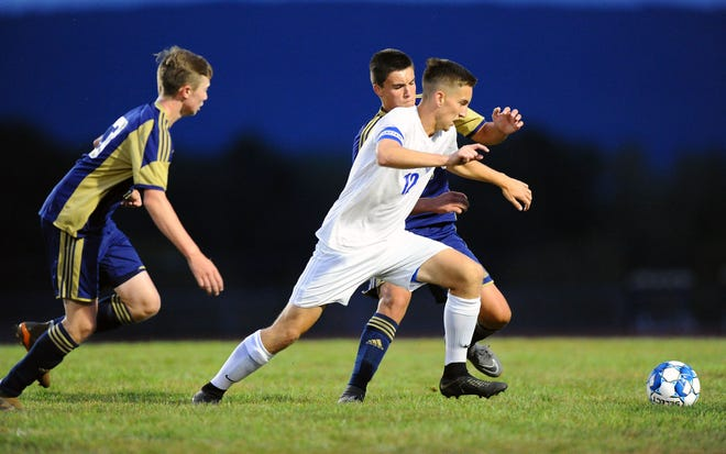 Trey McCumber (12) of Cedar Crest moves the ball near the Elco goal in front of Elco defender Rheece Shuey (35) during first half action Saturday Sept. 8, 2018 at Elco High School.