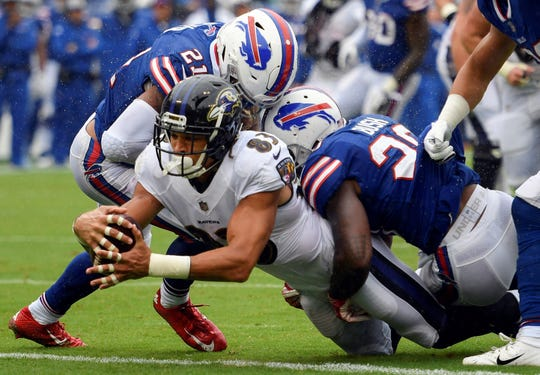 Baltimore Ravens wide receiver Willie Snead (83) dives between Buffalo Bills defensive back Jordan Poyer (21) and defensive back Rafael Bush (20) for a touchdown during the second half of an NFL football game Sunday, Sept. 9, 2018, in Baltimore. (AP Photo/Nick Wass)