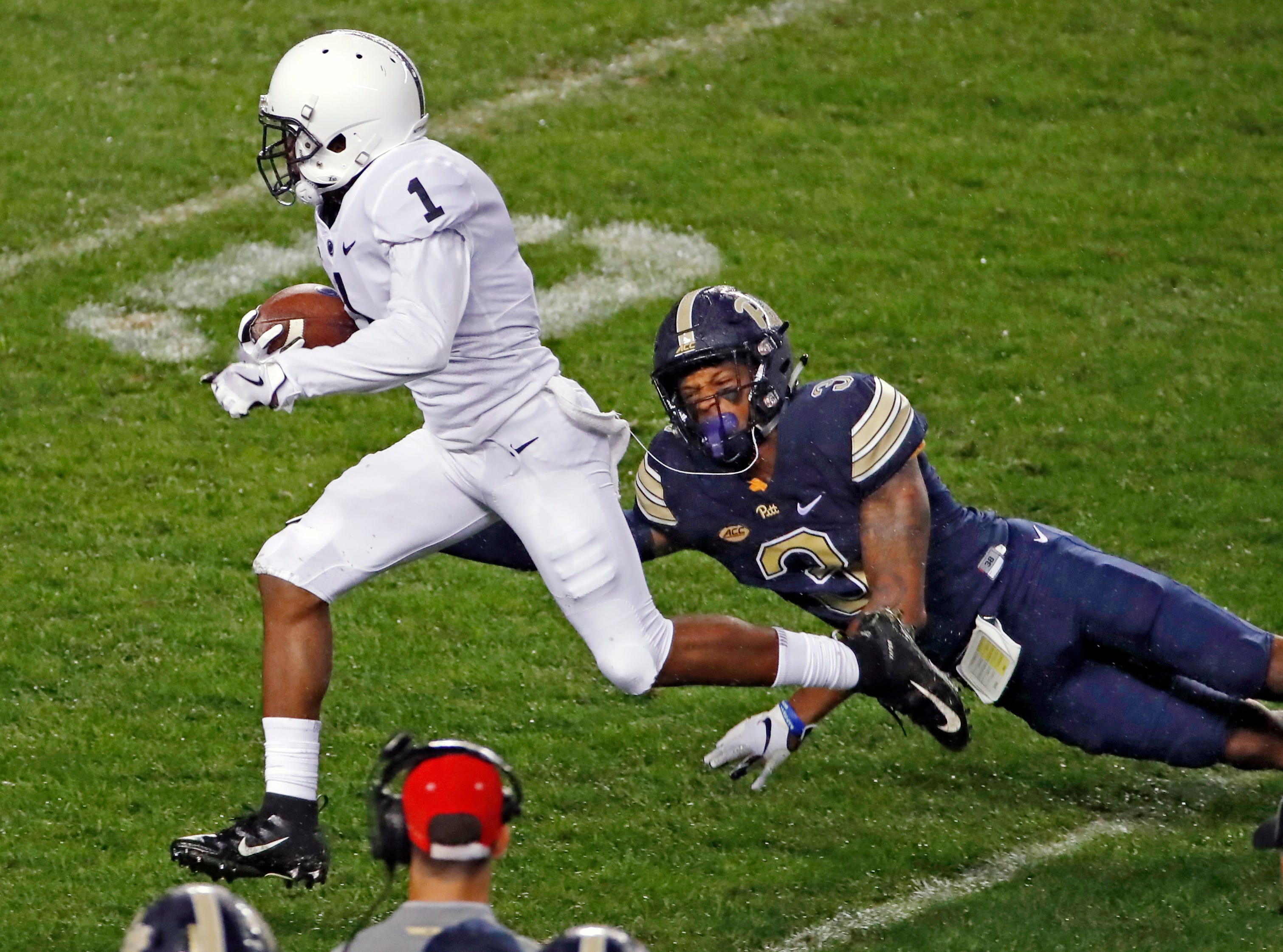 Penn State wide receiver KJ Hamler (1) runs through a tackle-attempt by Pittsburgh defensive back Damar Hamlin (3) en route to a touchdown during the first half of an NCAA college football game in Pittsburgh, Saturday, Sept. 8, 2018.