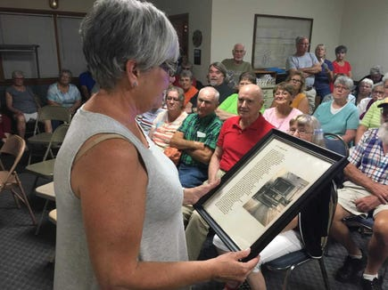 Mary Baum reads the poem from a framed clipping and picture at a recent Northeastern York County History in Preservation - NEYCHIP - presentation.