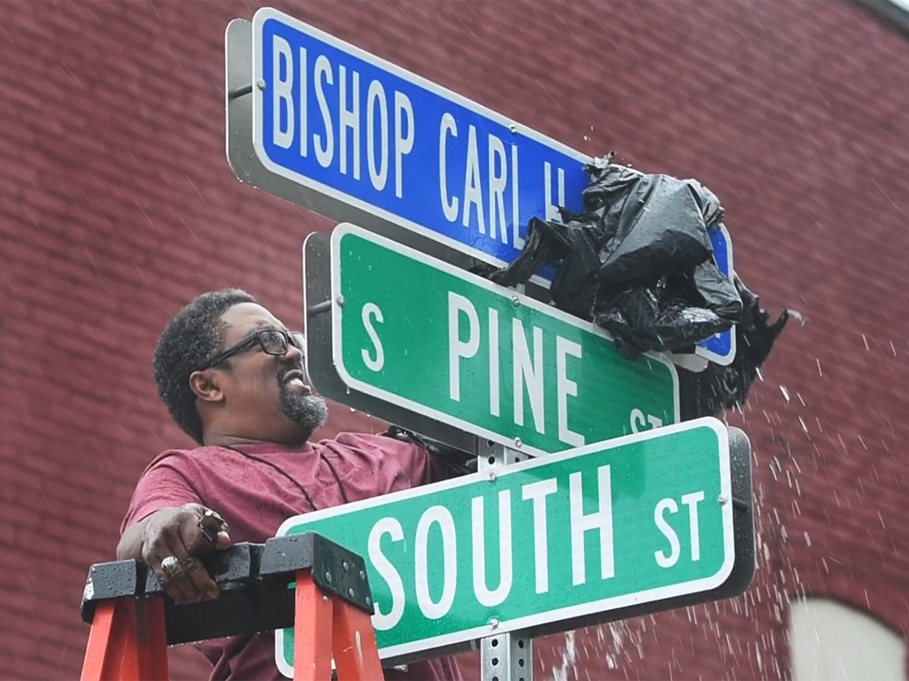 Stephon Scott, the son of Bishop Scott, unveils a new sign honoring Bishop Carl H. Scott at Pine and South Streets in York in the rain Sunday.