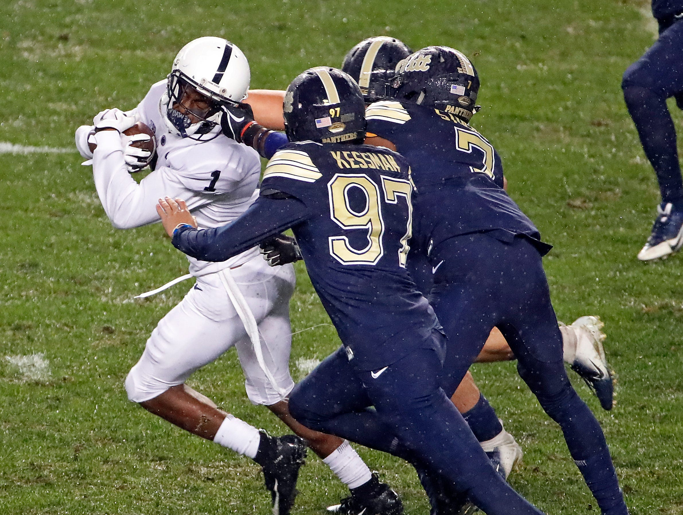 Penn State wide receiver KJ Hamler (1) is hauled down by the face mask by Pittsburgh defensive back Jazzee Stocker (7) during the first half of an NCAA college football game in Pittsburgh, Saturday, Sept. 8, 2018. A penalty was called against Pittsburgh.