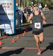 Tyler Sickler crosses the finish line to win the 50th Annual Journal Jog in Reno  on Sunday.