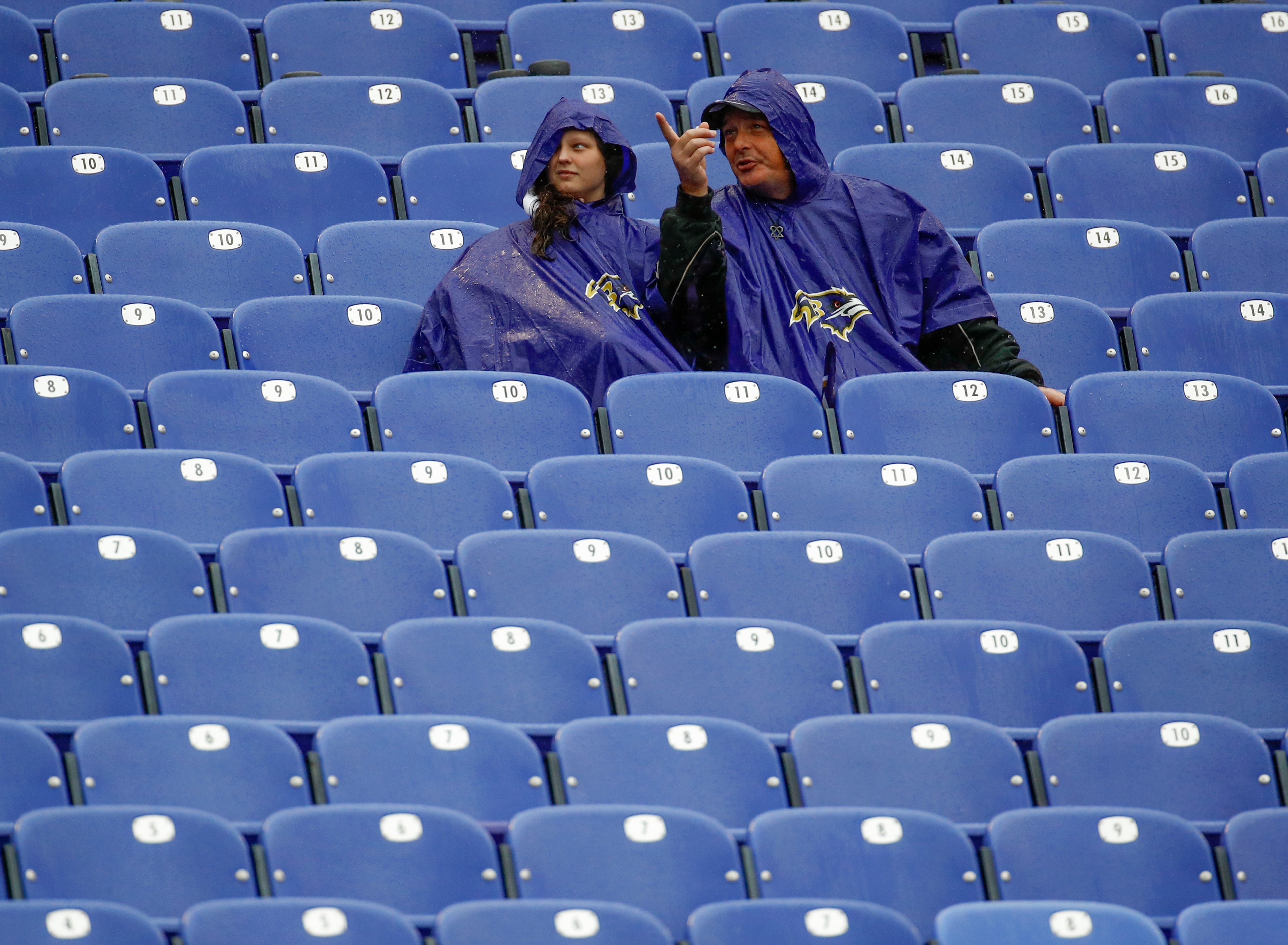 Baltimore Ravens fans watch team warm ups during a rain storm before the NFL football game between the Baltimore Ravens and the Buffalo Bills, Sunday, Sept. 9, 2018 in Baltimore. (AP Photo/Patrick Semansky)