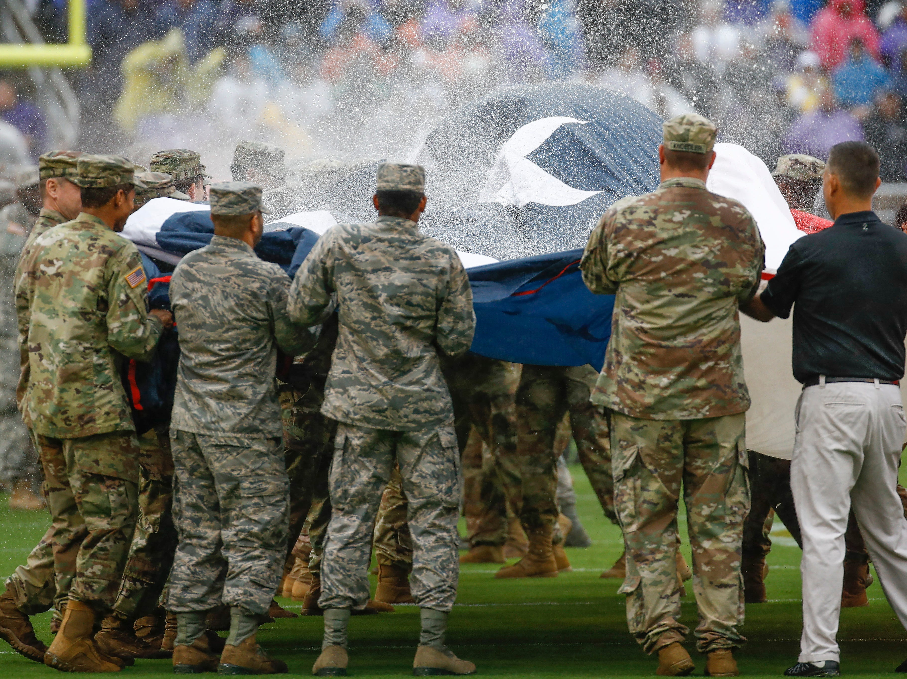 Military personnel shake water off of a United States flag after the playing of the national anthem before an NFL football game between the Baltimore Ravens and the Buffalo Bills, Sunday, Sept. 9, 2018 in Baltimore. (AP Photo/Patrick Semansky)
