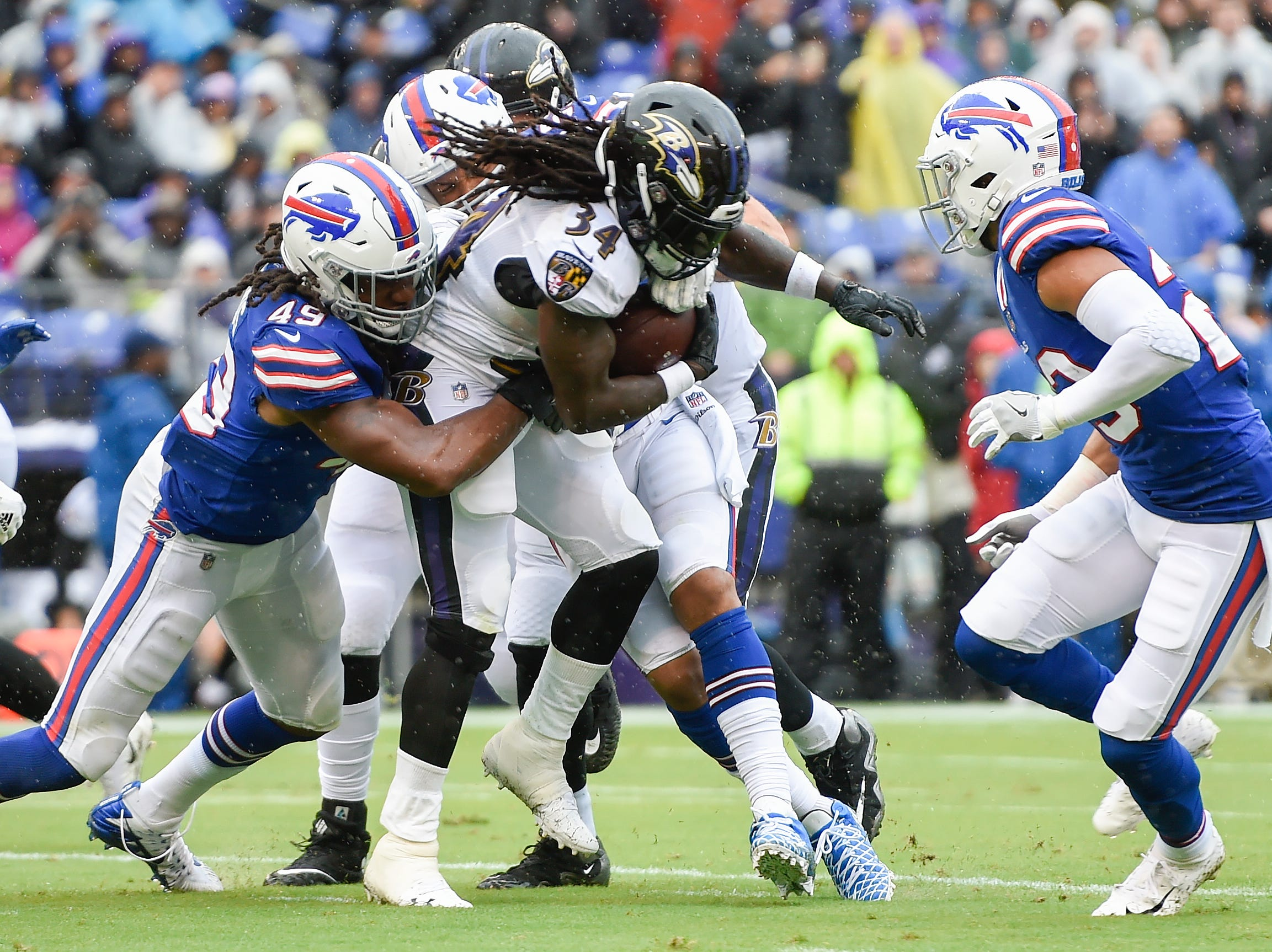 Buffalo Bills linebacker Tremaine Edmunds (49) hangs onto Baltimore Ravens running back Alex Collins (34) who carries the ball toward the end zone for a touchdown during the first half of an NFL football game Sunday, Sept. 9, 2018 in Baltimore. (AP Photo/Gail Burton)