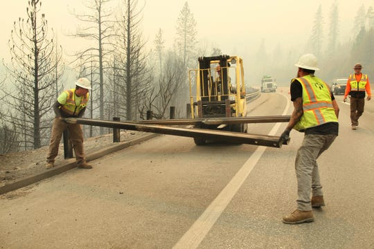 Highway Specialty Co. workers on Saturday afternoon, Sept. 8, 2018 repair wooden posts on the guardrails the Delta Fire burned out along I-5 south of Lamoine. (Hung T. Vu/ Special to the Record Searchlight)